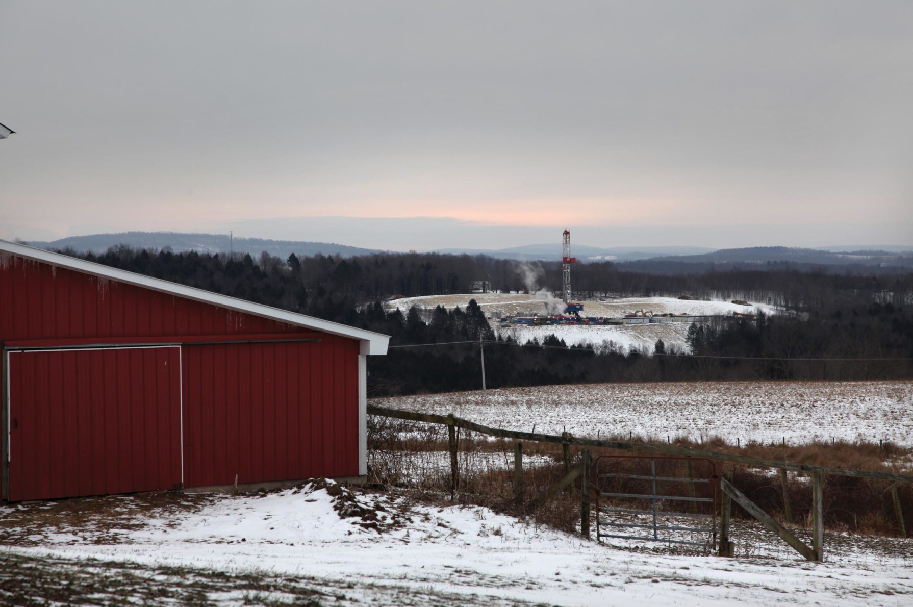 Red barn on a snowy farm, with a fracking well in the distance.