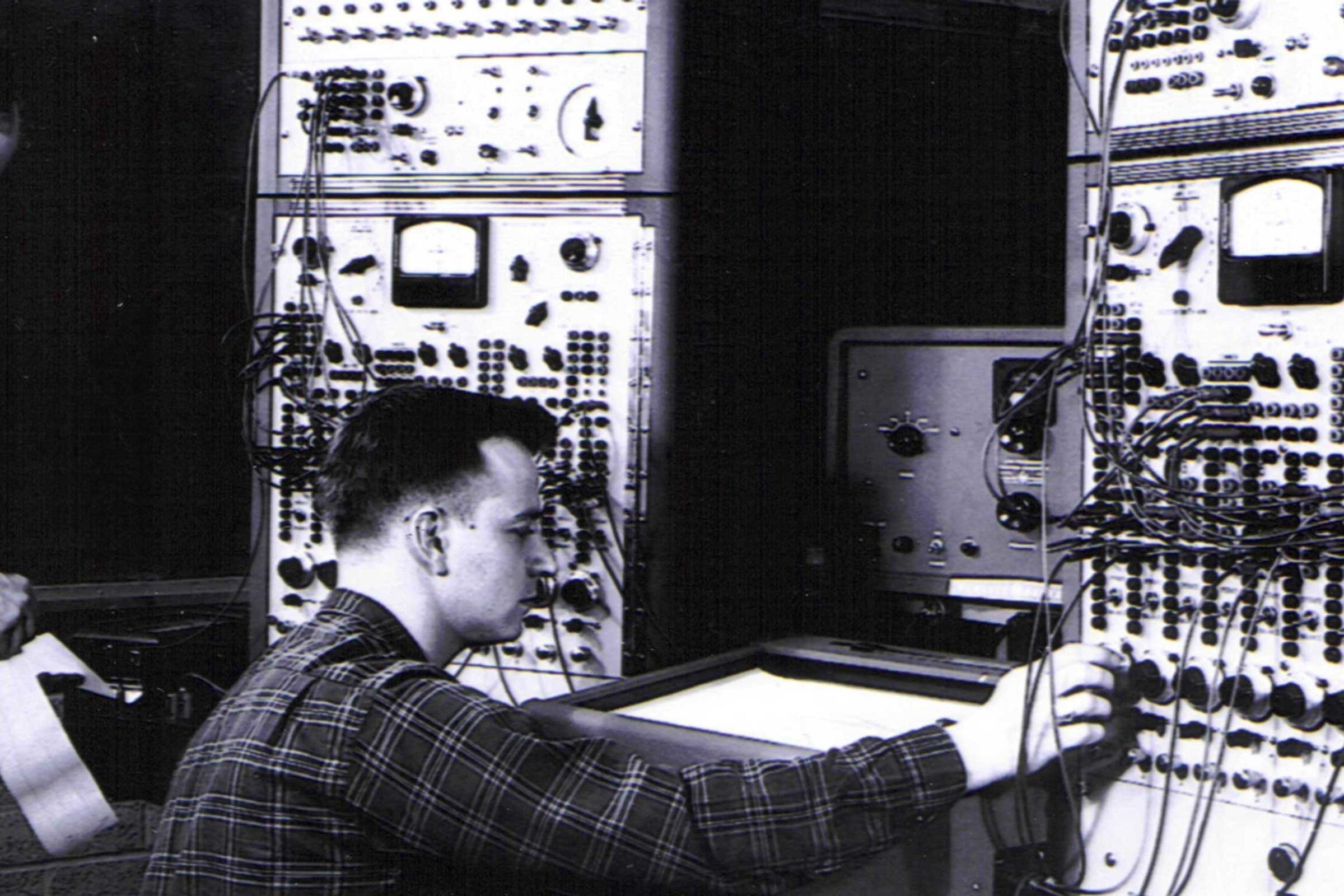 Black and white photo of researchers working on a computer at Applied Dynamics