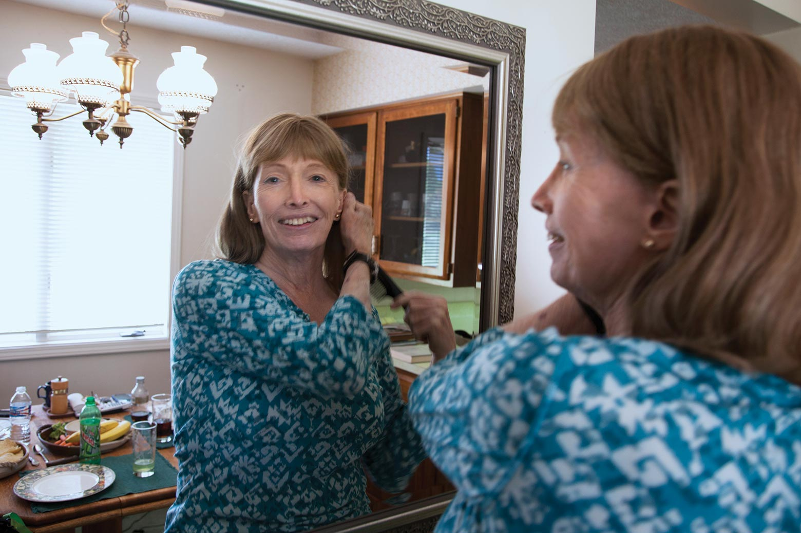 A woman brushes her hair while looking in a mirror.