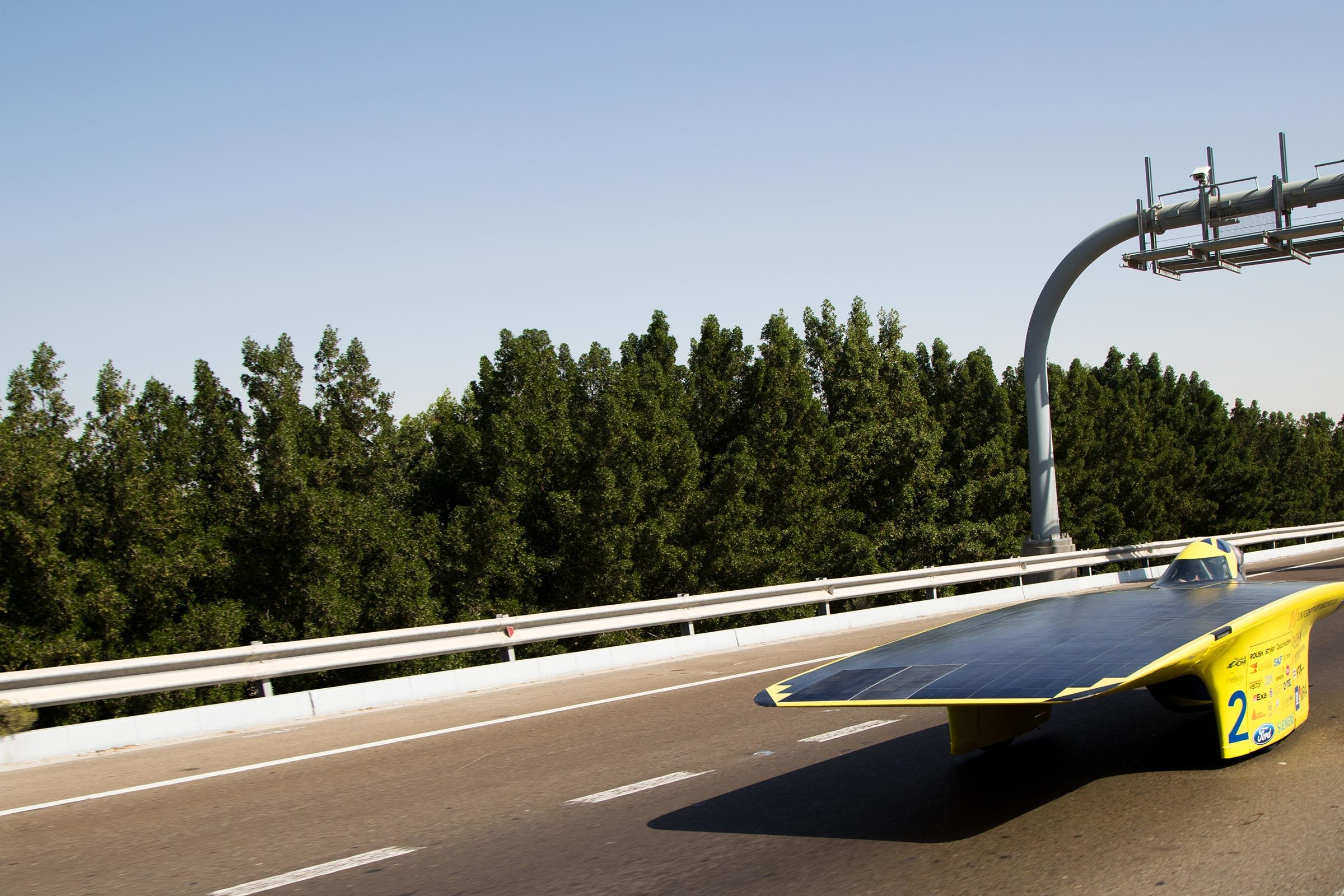 Solar car racing on a road.