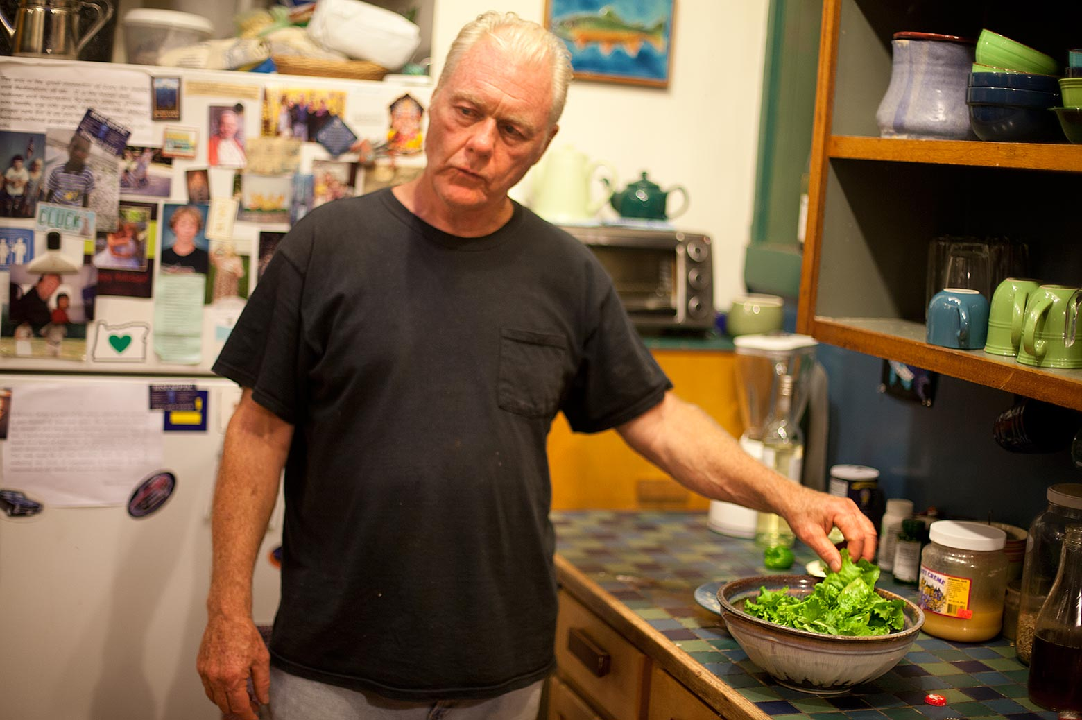 Man in kitchen making salad