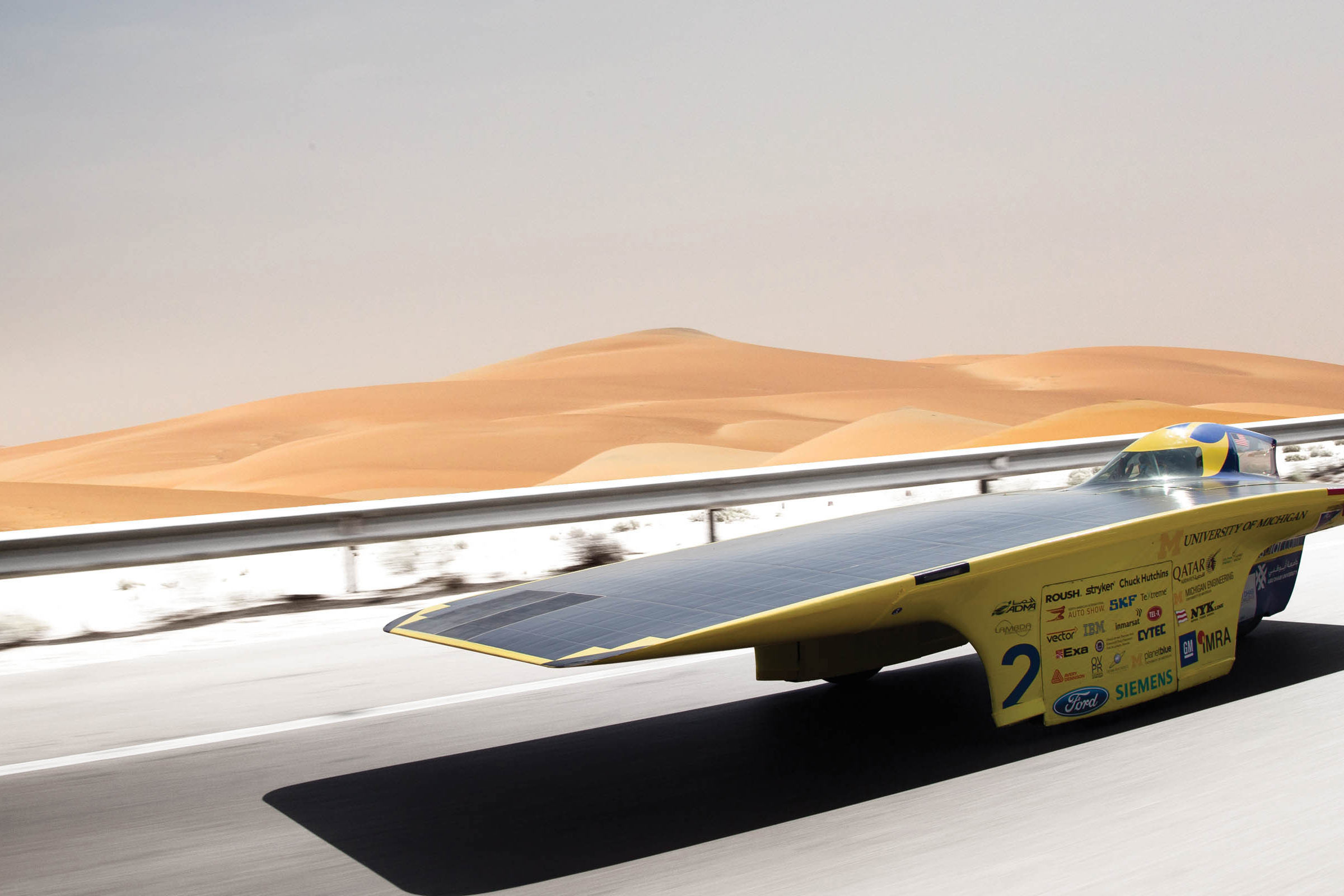 Solar car drives on desert highway.