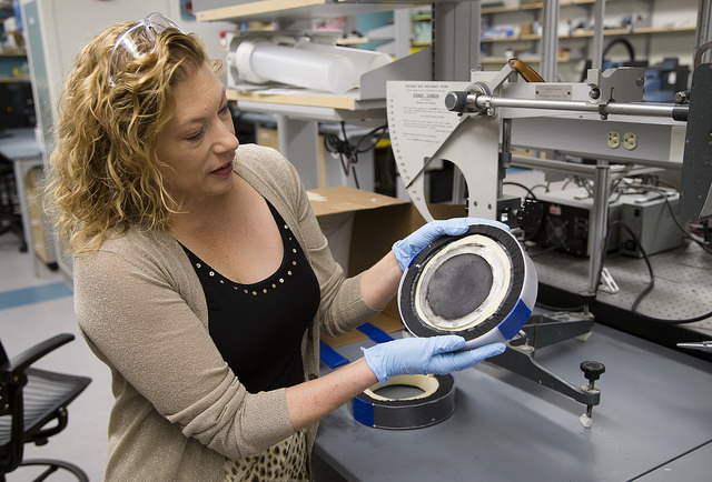 Woman in lab holds helmet