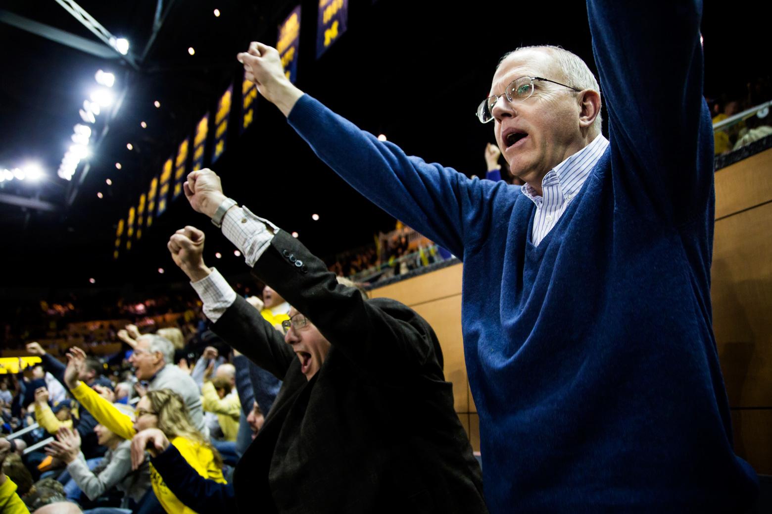 Dave Munson celebrating a Michigan basketball victory with Michigan Engineering alumnus Randy Brouckman