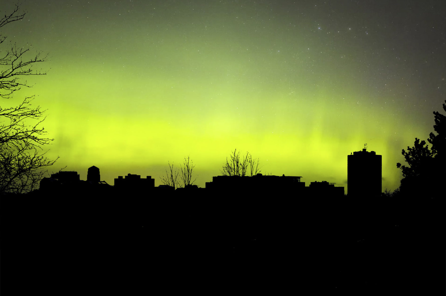A manufactured photograph of a blacked out Ann Arbor skyline with a green aurora filling the sky.