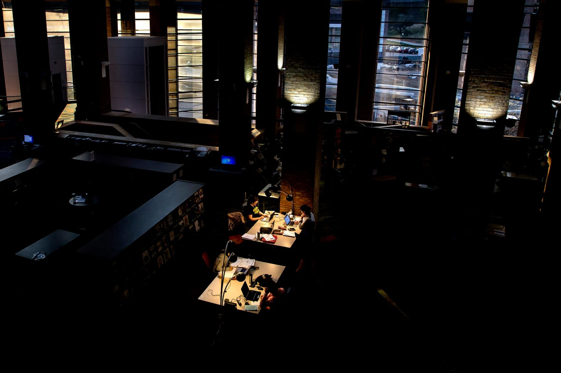 Two desks lit with lamps in a darkened study center. Students study and fall asleep on the desks.