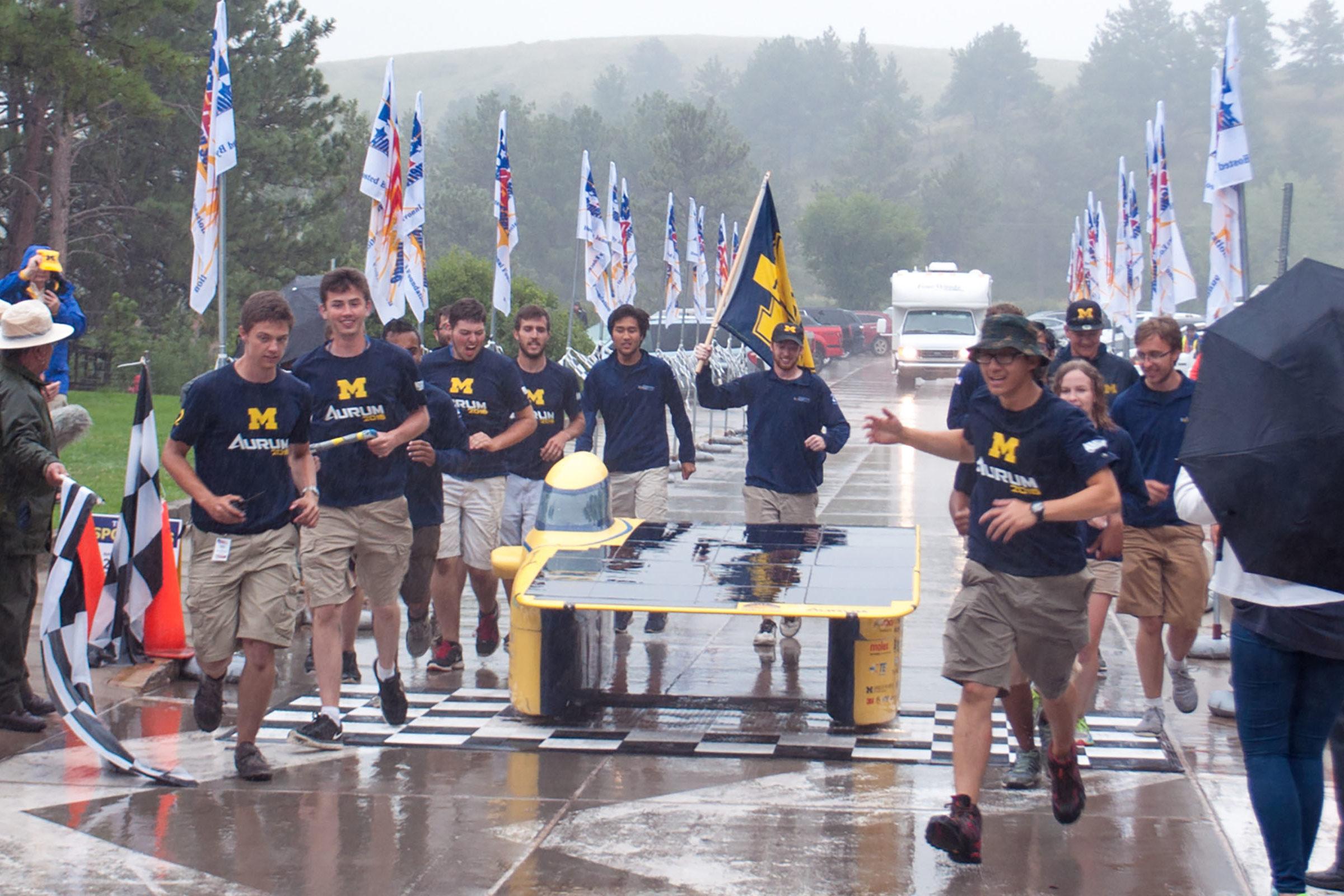 Members of the Michigan Solar Car team run across a finish line alongside their car, Aurum, in the rain.