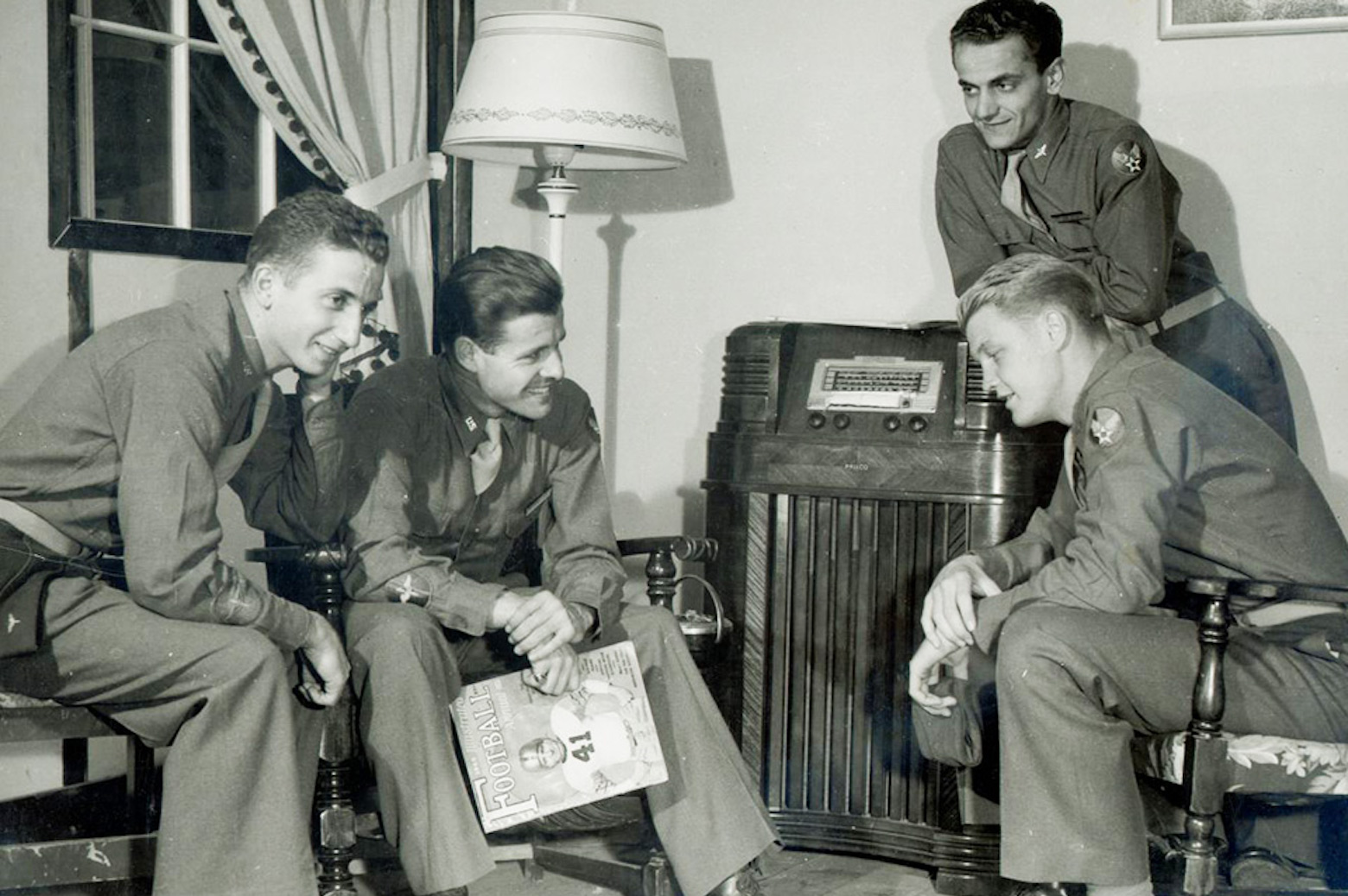 group of soldiers sitting around radio listening to Michigan football game