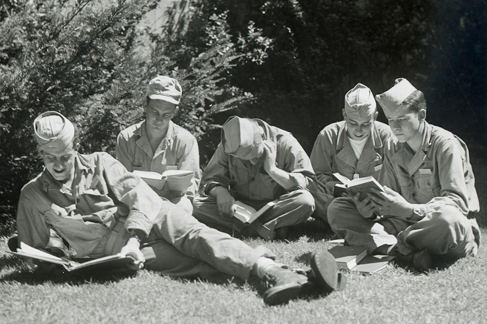 group of soldiers sitting on grass reading