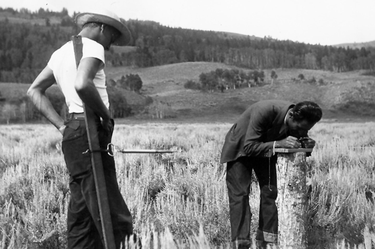 2 men in surveying a field