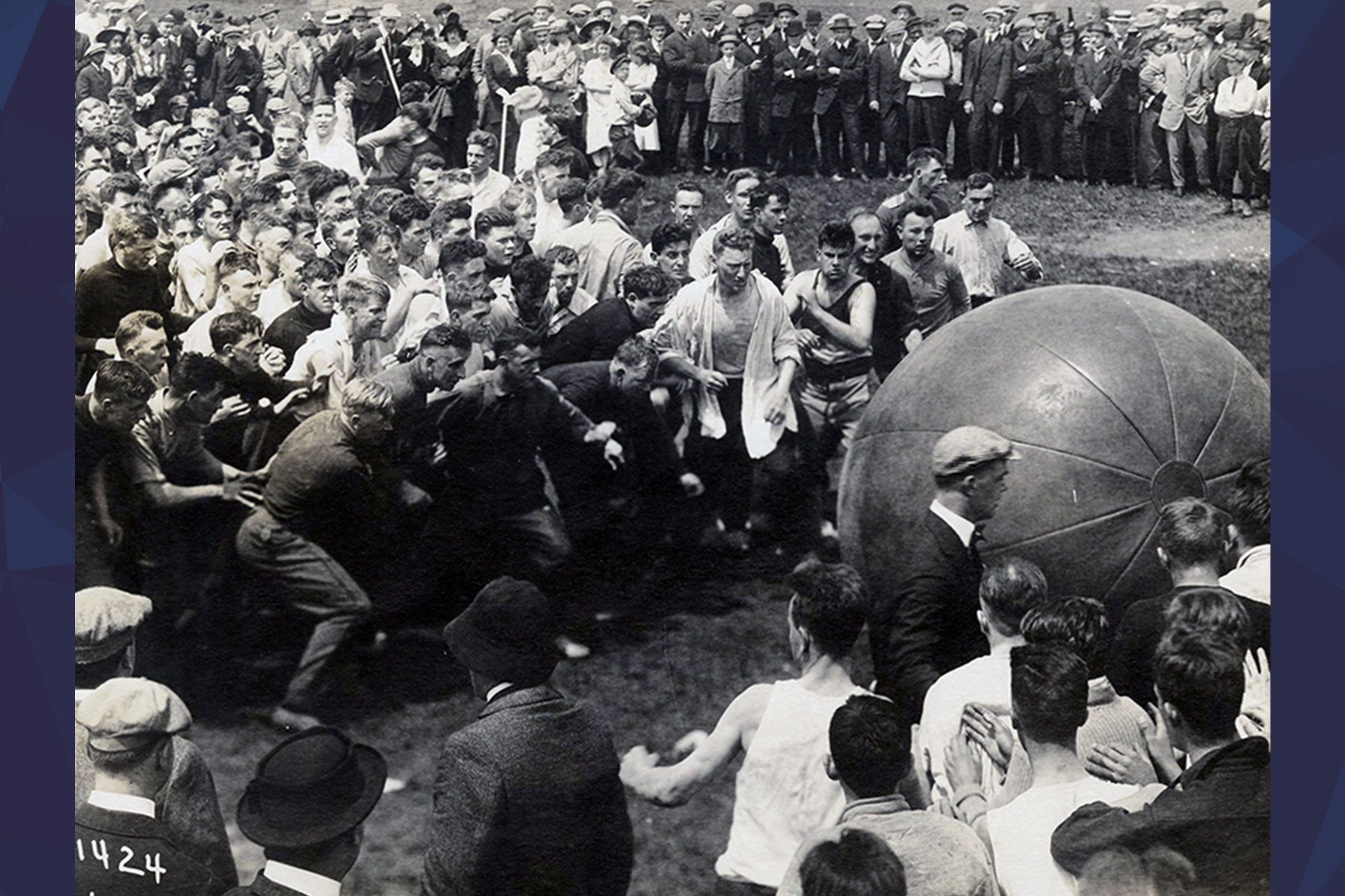 Black and White picture of vulcans in two teams pushing a giant ball