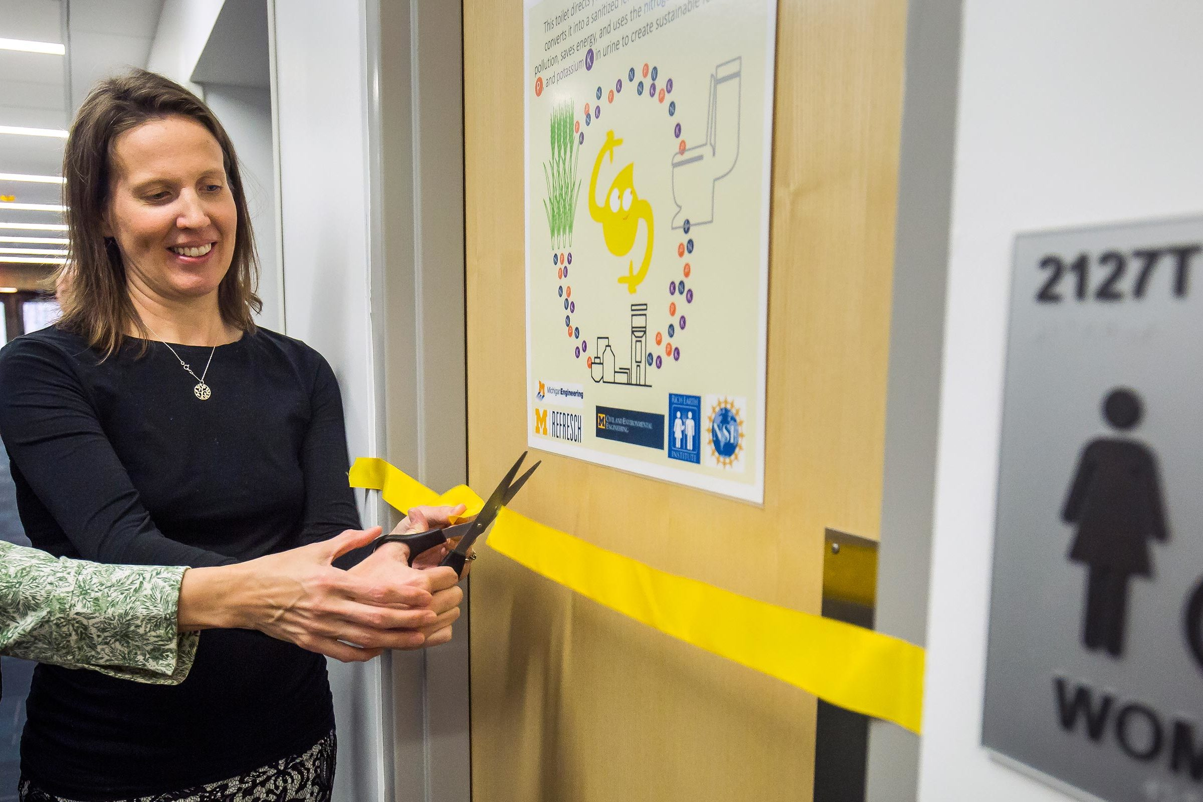 Two professors cut the ribbon to officially open the new restroom