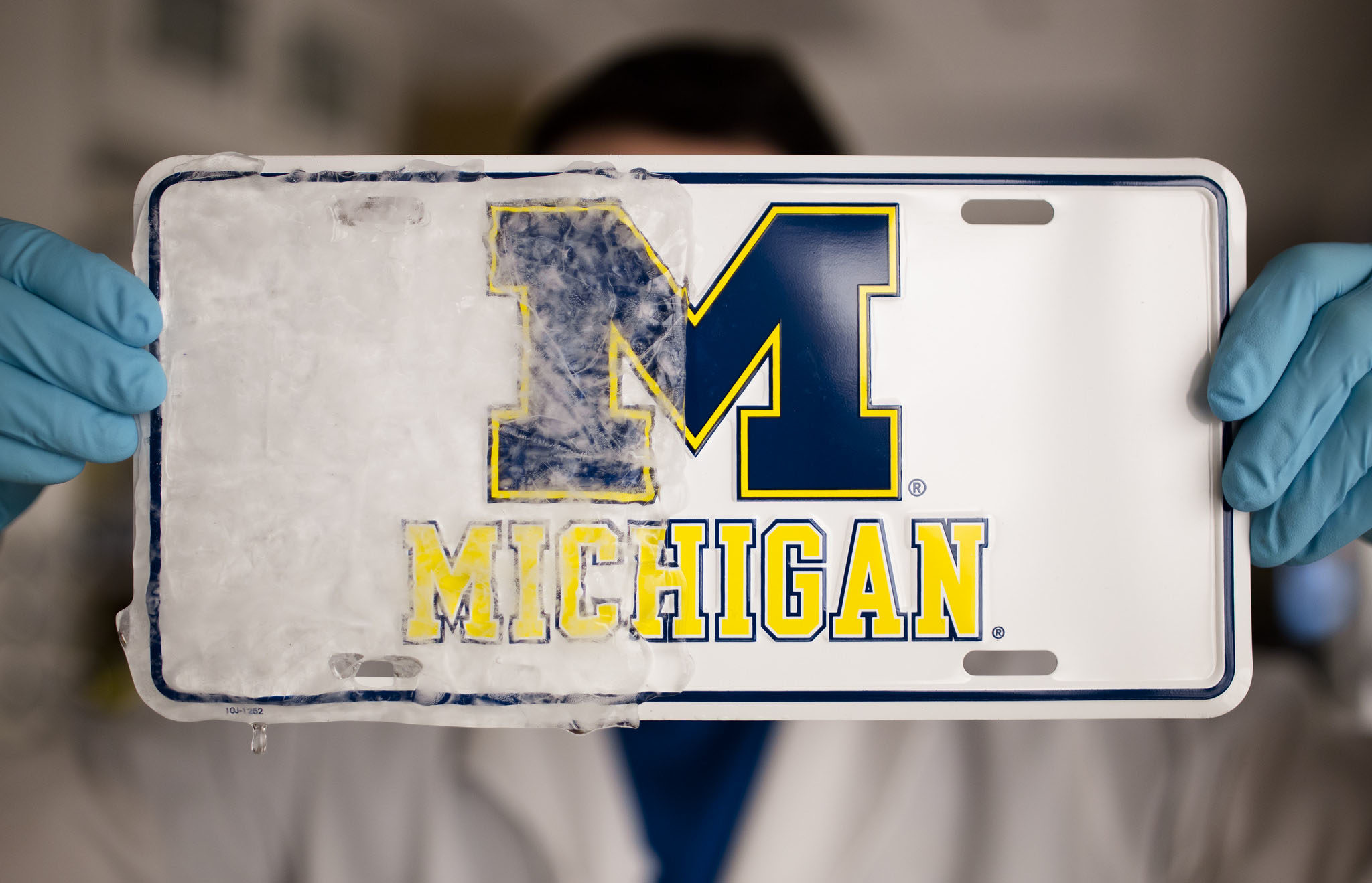 A photograph of Kevin Golovin, a graduate student in Materials Science and Engineering, golding a license plate that is half covered in ice.