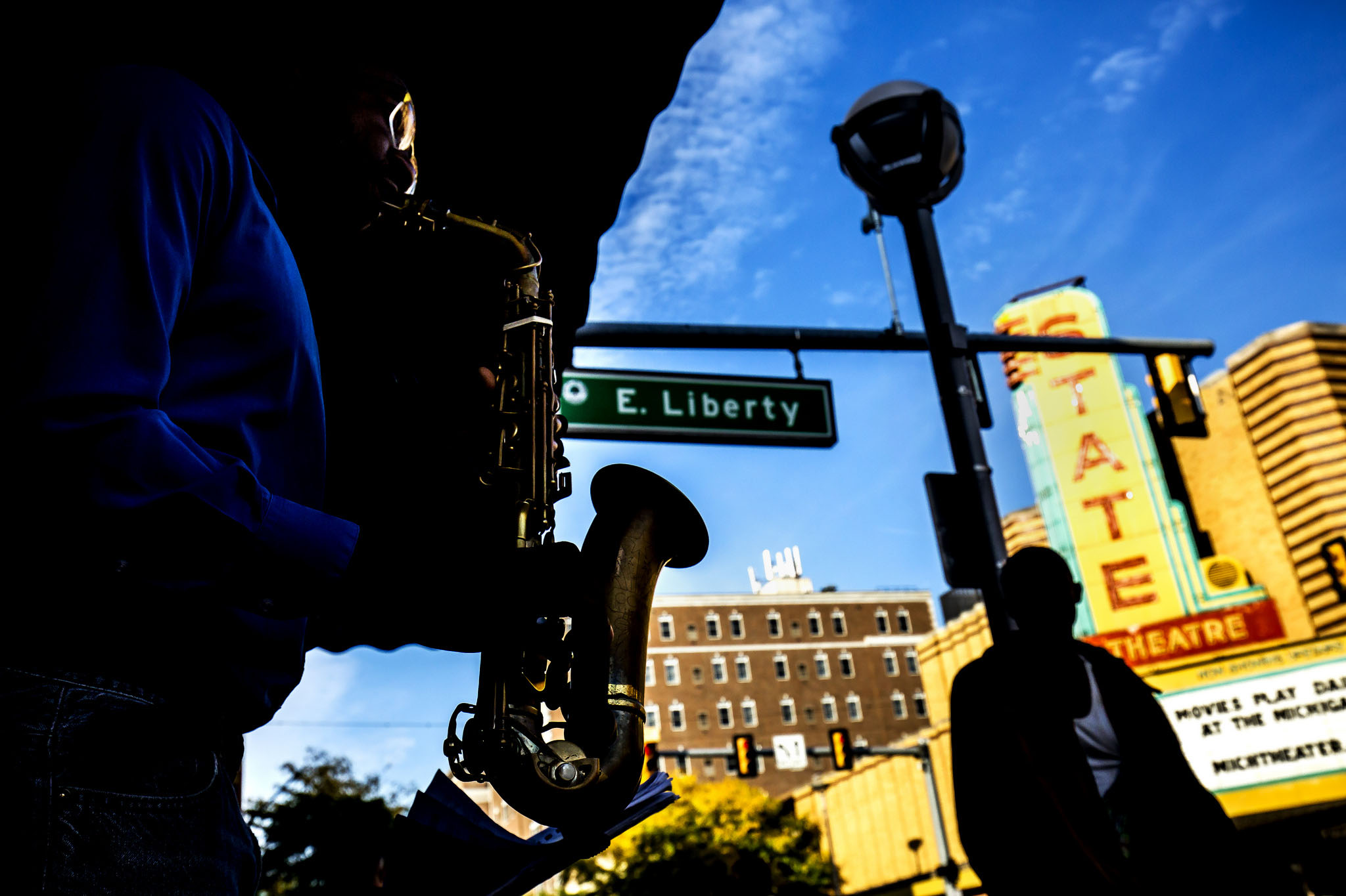 A photograph of Ahmid Alexander playing saxophone on State Street.