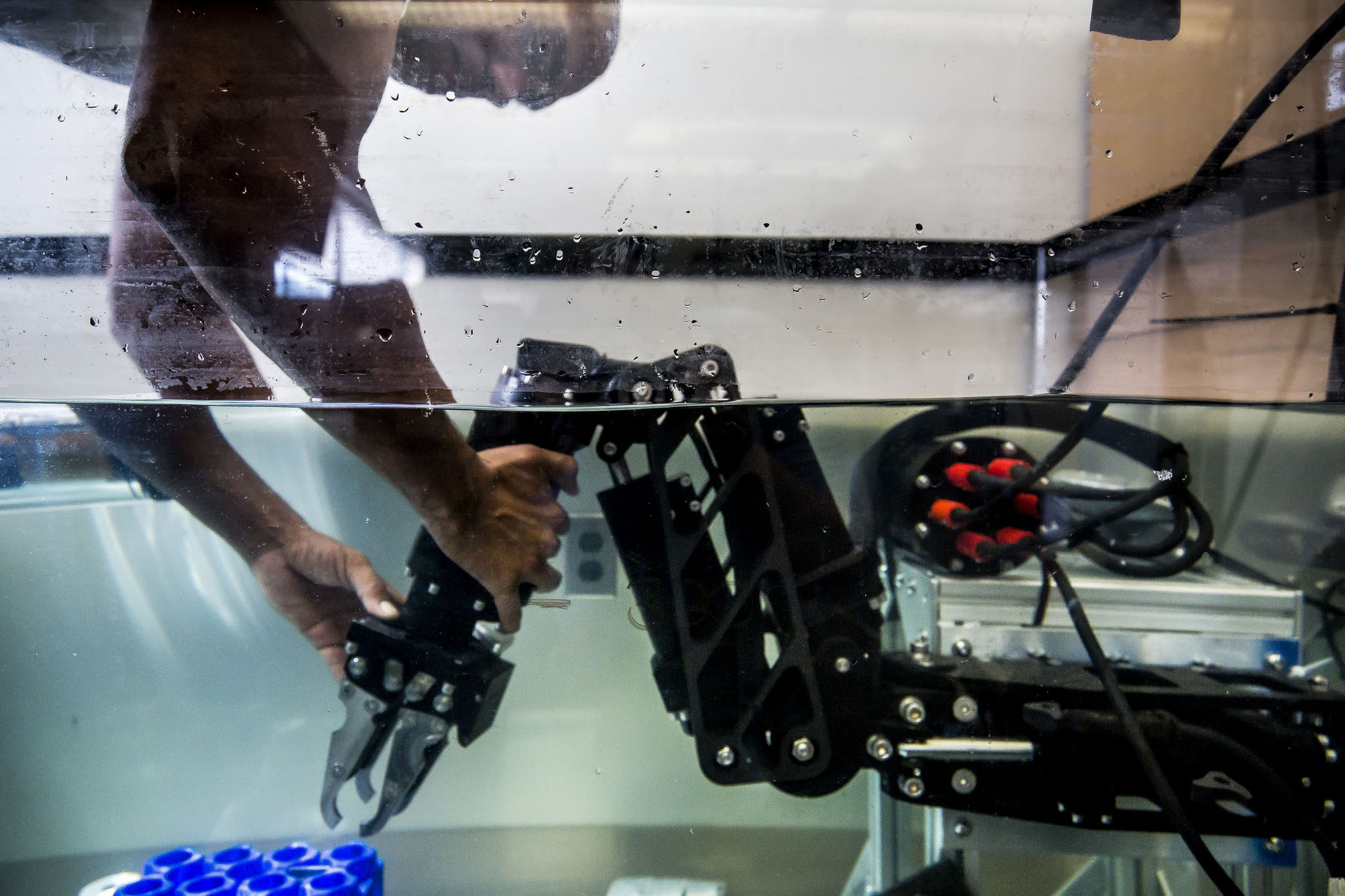 A photograph of Matthew Johnson-Roberson, Assistant Professor of Naval Architecture and Marine Engineering, working with a underwater robot arm system.