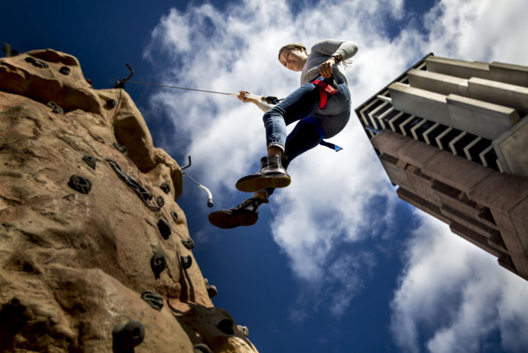 A photograph of a student climbing a rock tower.