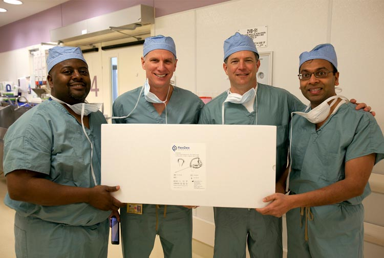 From left: Eugene Thomas, James Geiger, Greg Bowles and Shorya Awtar hold an unopened package with a FlexDex instrument inside as they stand outside of a University of Michigan Hospital surgery room where the instrument will be used for the first time in surgery