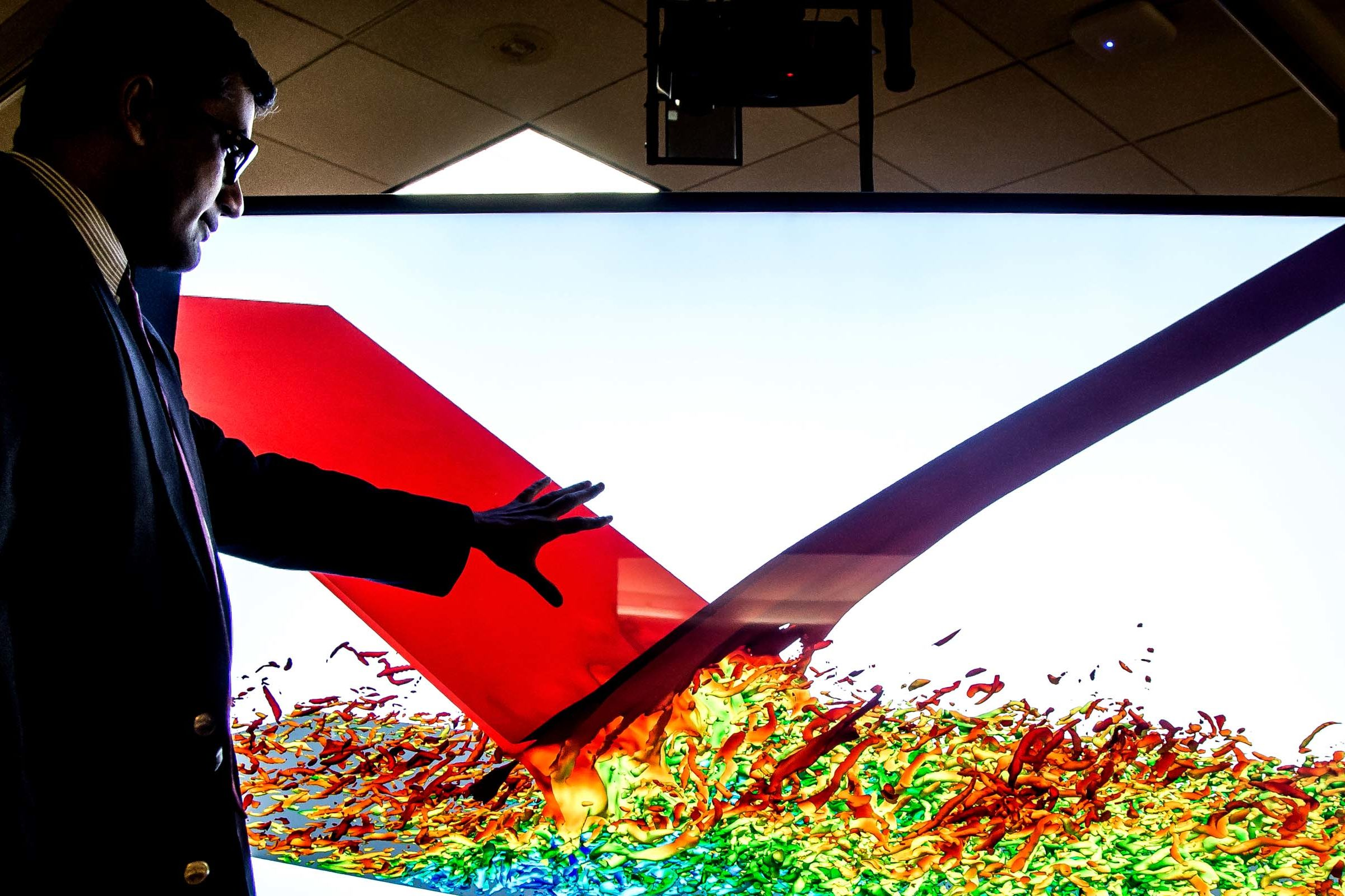 Professor Karthik Duraisamy reaches toward a large monitor showing a colorful data simulation
