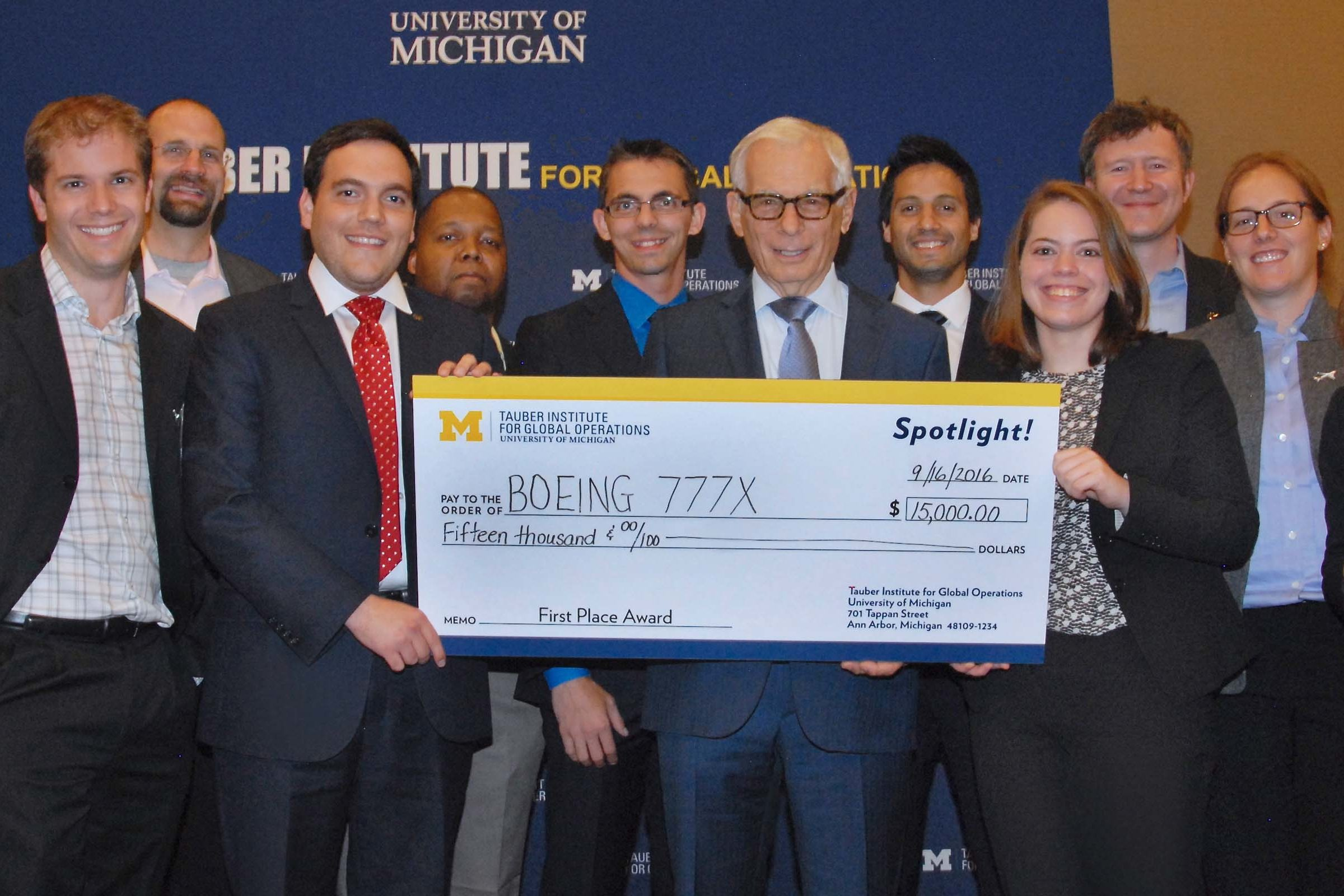 A group of people pose for a photo with a large check.