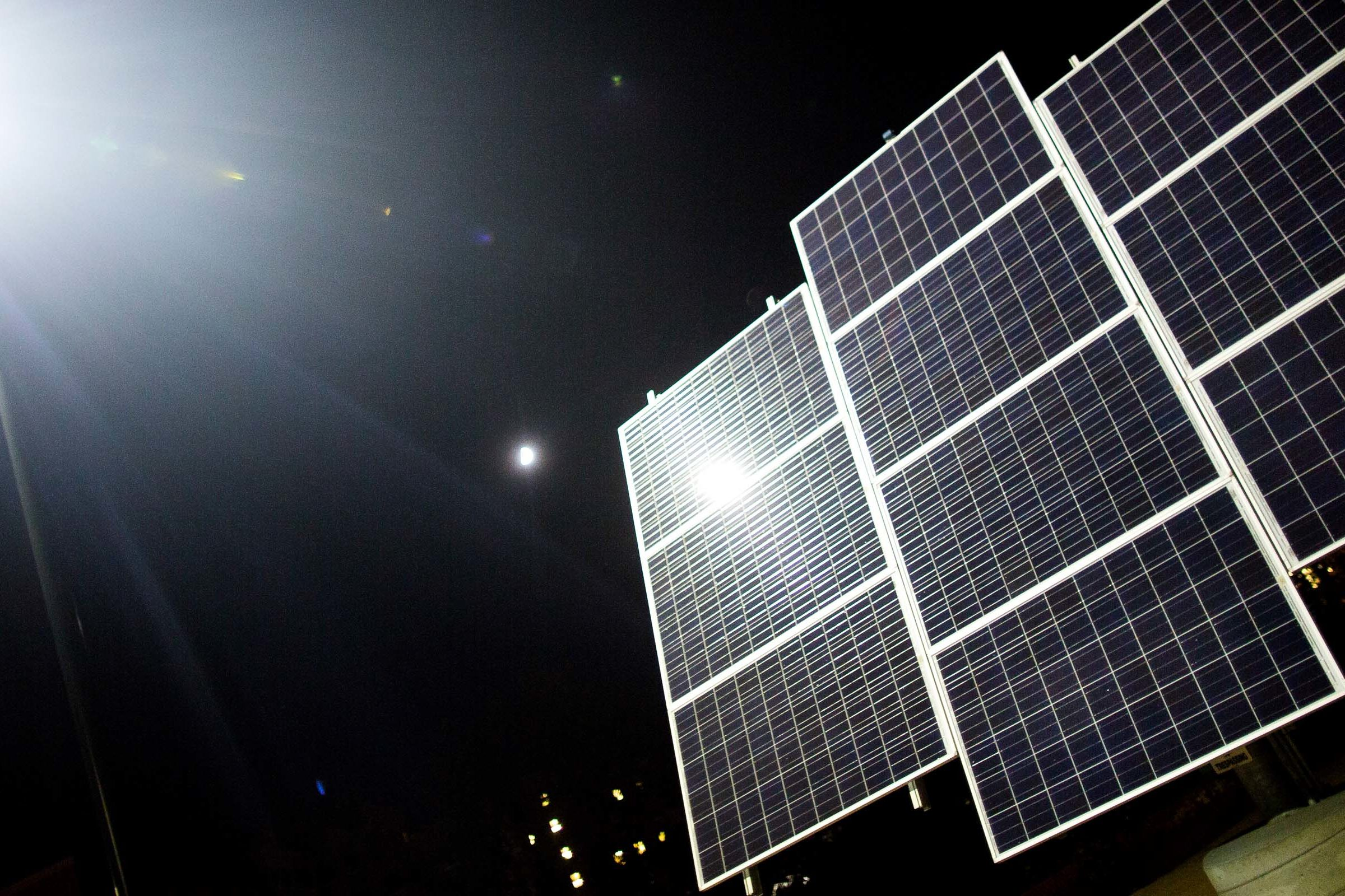 A solar panel illuminated at night.