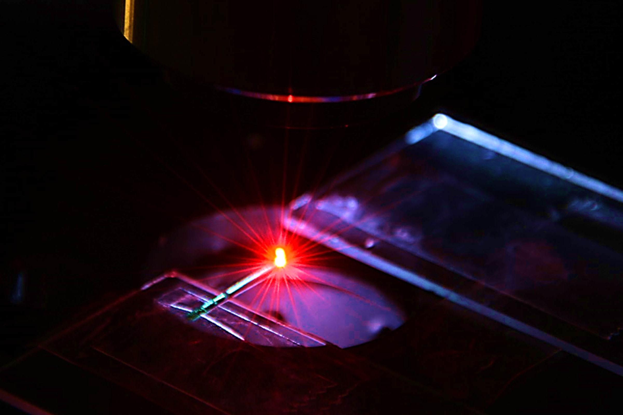Red laser light hits glass slide.