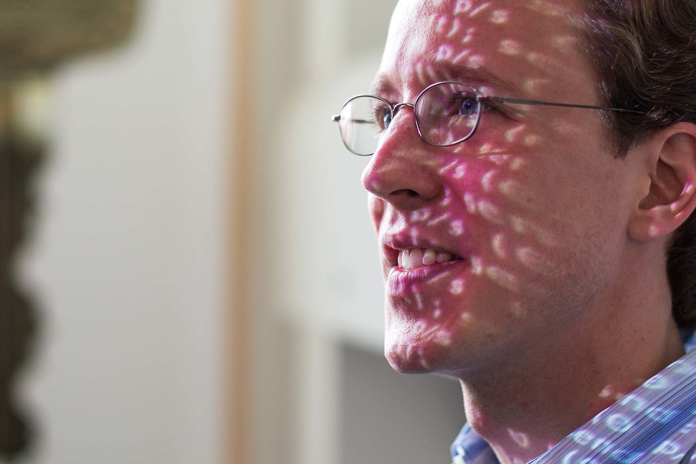 J. Alex Halderman in his office with ZMap characters projected over his face. Photo: Joseph Xu, Michigan Engineering.