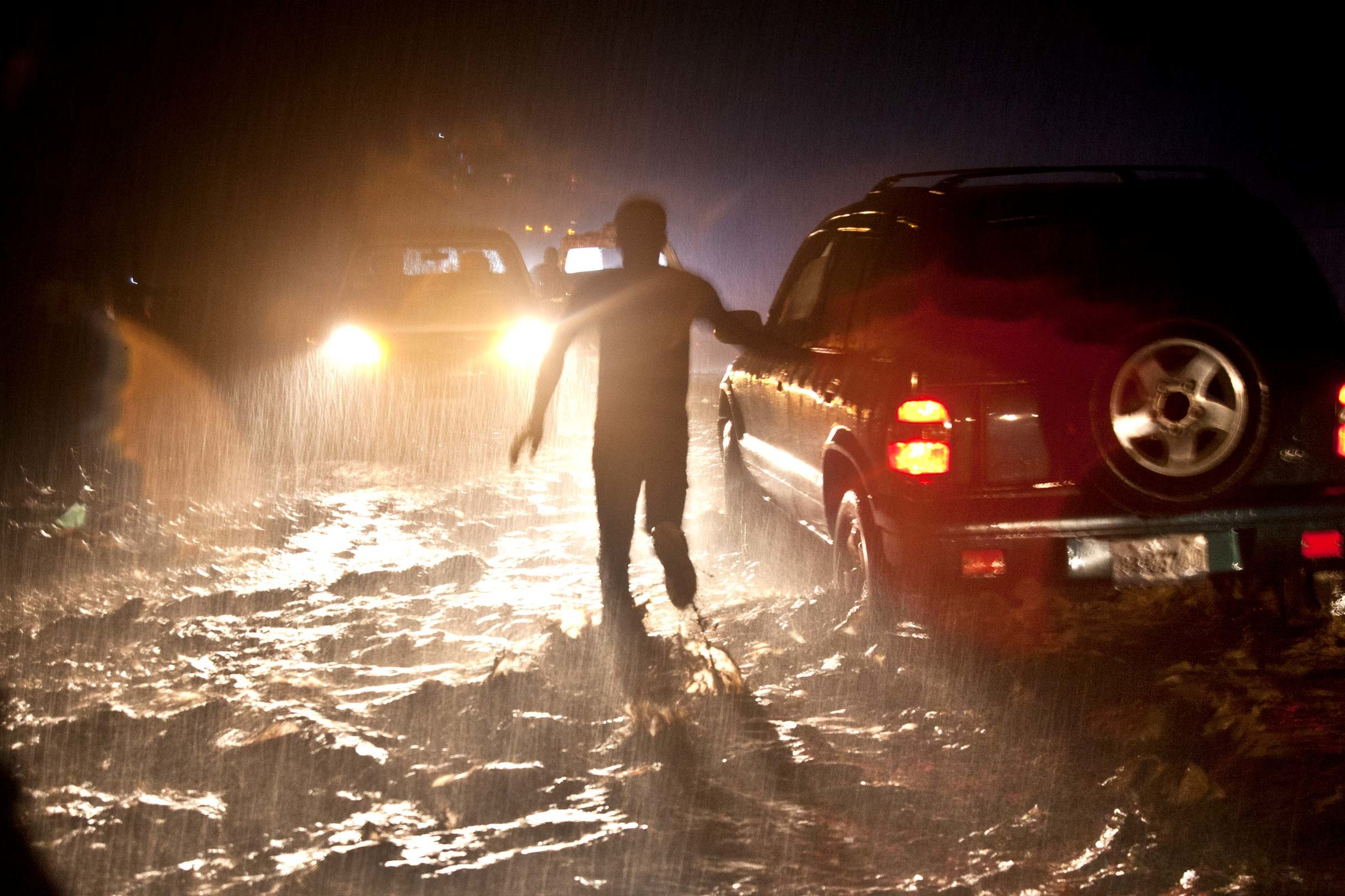 Corinne Joachim-Sanon and her team are caught in a major downpour that floods the outskirts of Cap Haitian and halts the traffic to a stop. Ouanaminthe, Haiti, November 2016. Photo: Marcin Szczepanski, Michigan Engineering.