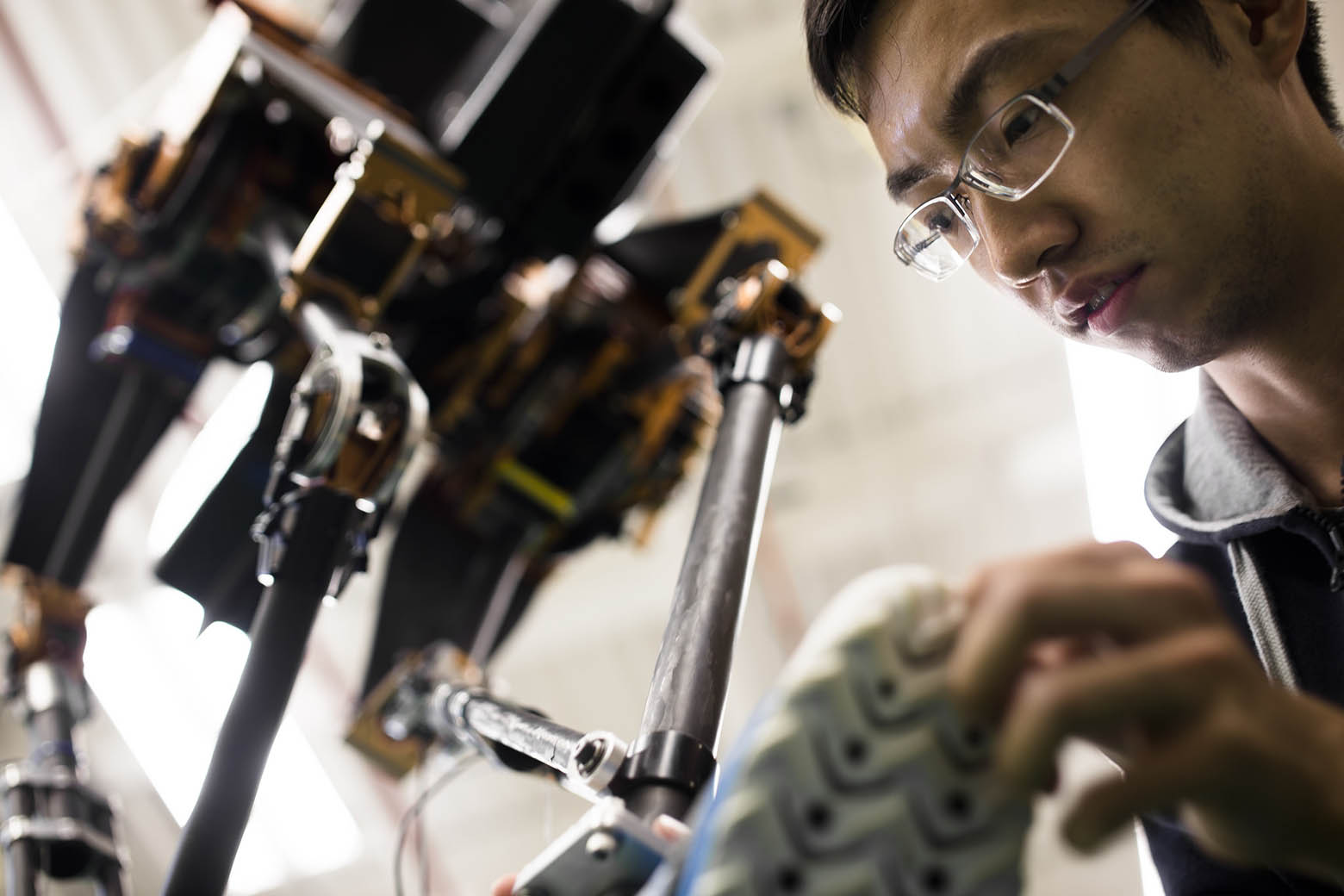 "Xingye ""Dennis"" Da, a doctoral student in mechanical engineering, inspects the ankle of MARLO, a bipedal robot."