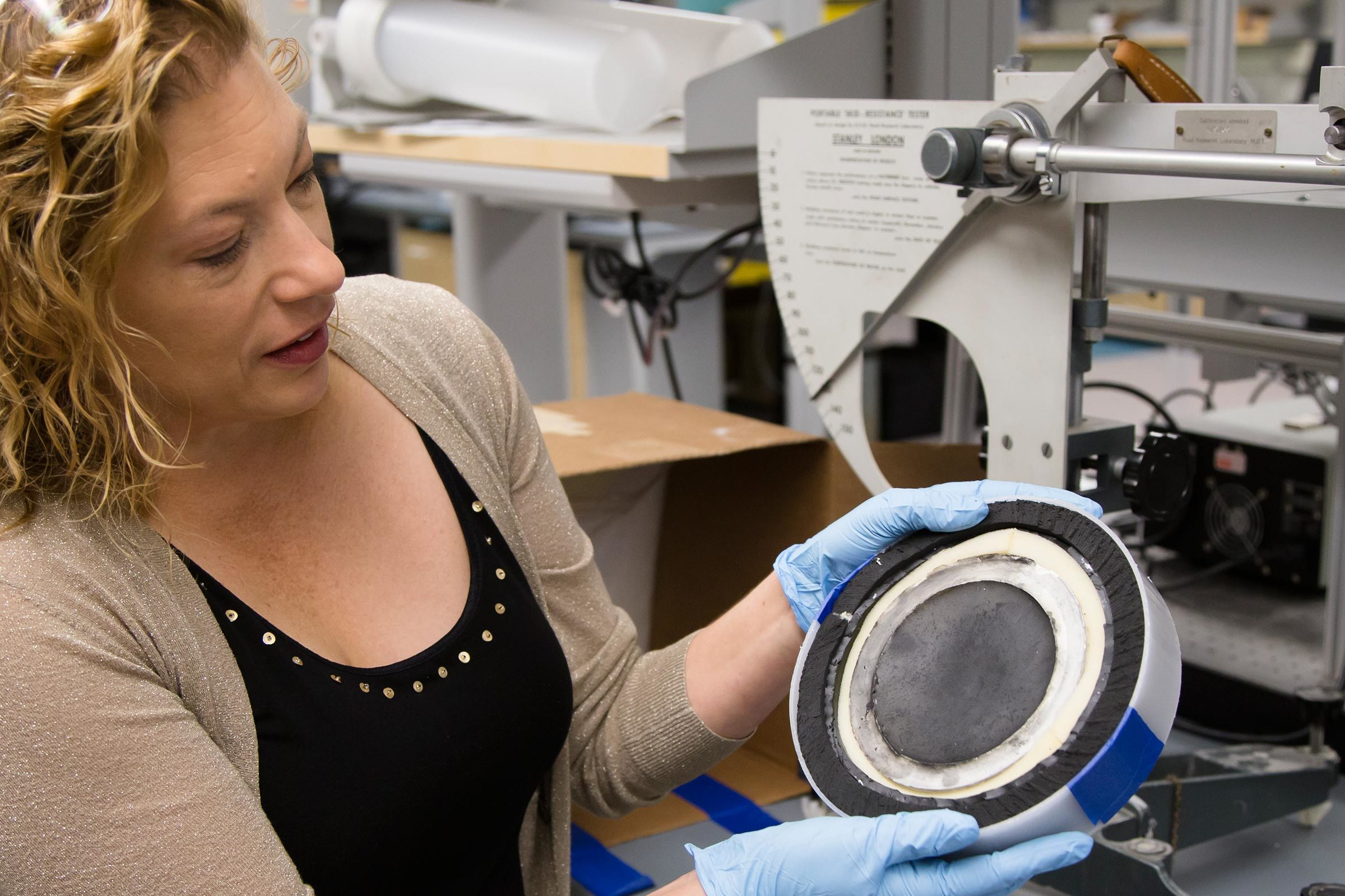 A woman holds a disk of concentric circles representing layers of the helmet.