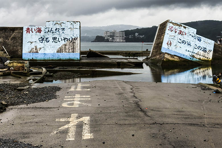 A dramatic image of a damaged sea wall in Japan months after a tidal wave broke through.