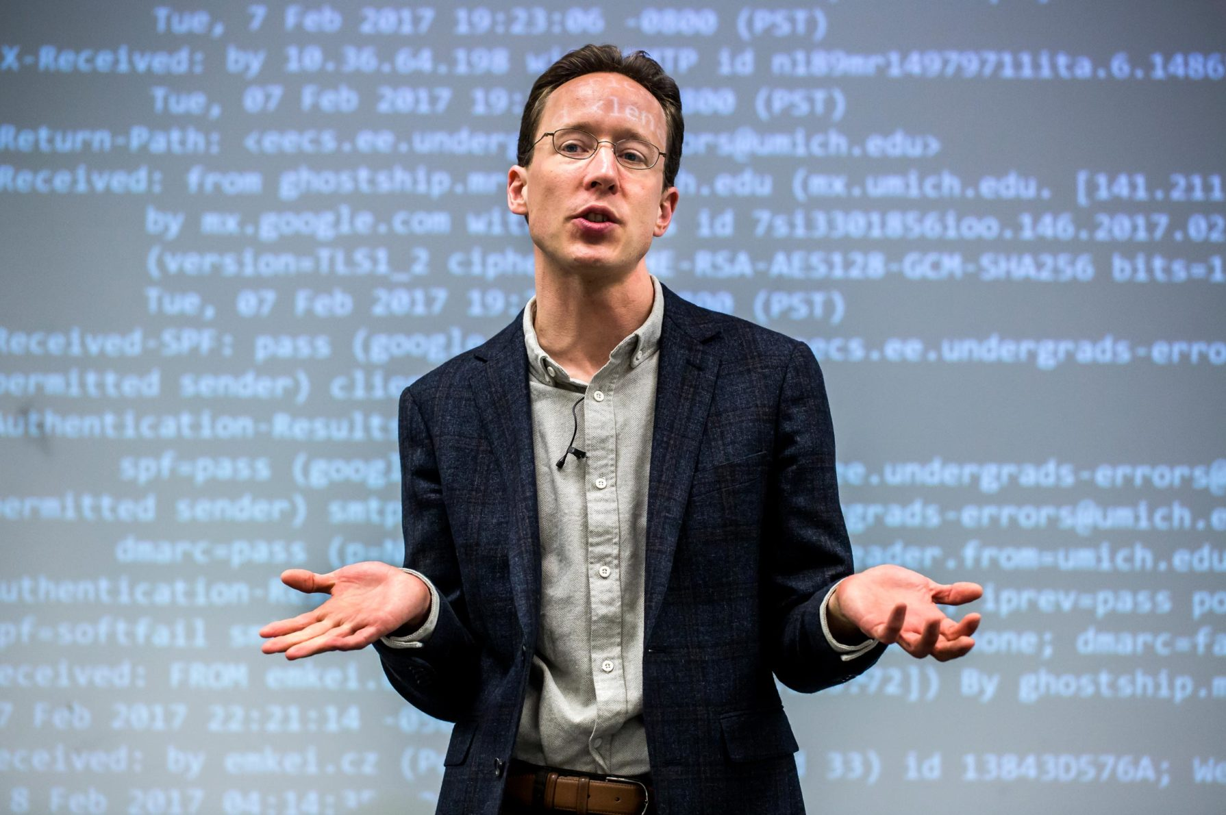 Portrait of J. Alex Halderman lecturing with projected text on the board behind him. Photo: Joseph Xu, Michigan Engineering.