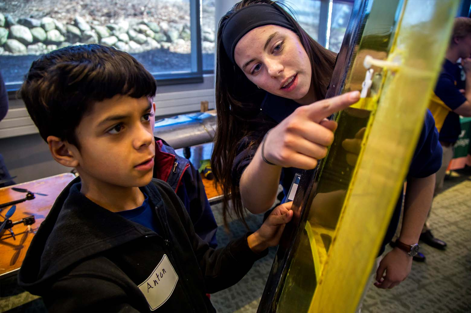 A female Michigan Engineering student shows a young boy the wing of a model plane.