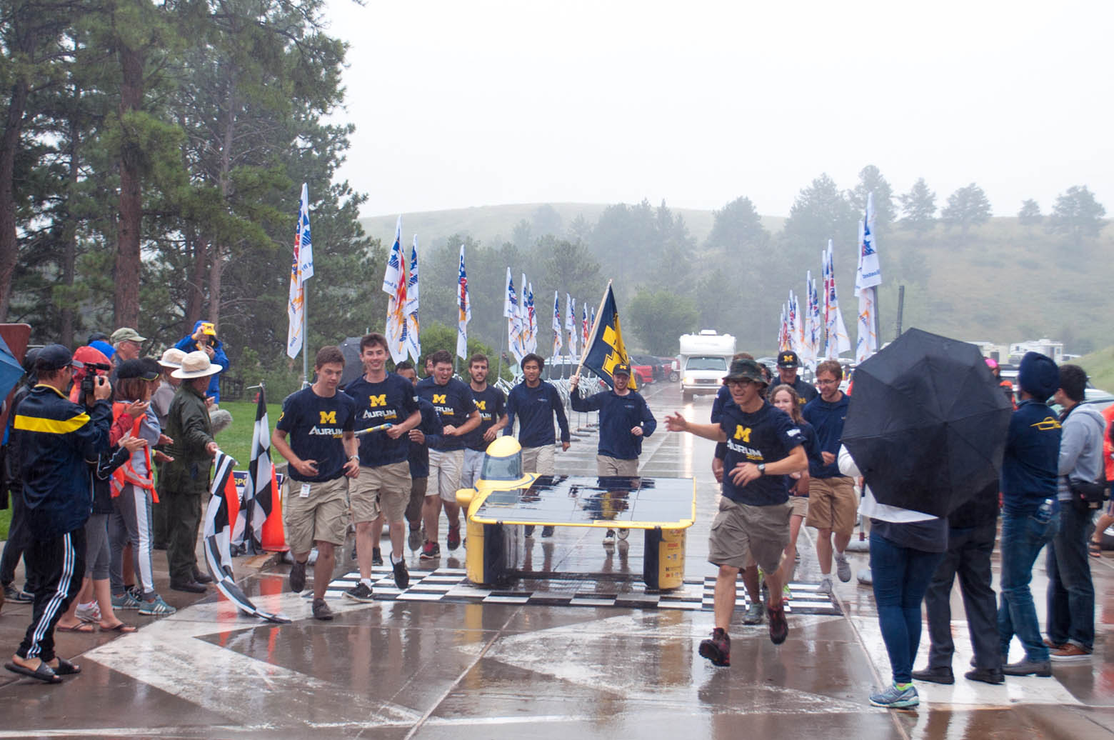 Members of the Michigan Solar Car team run across a finish line alongside their car, Aurum, in the rain.