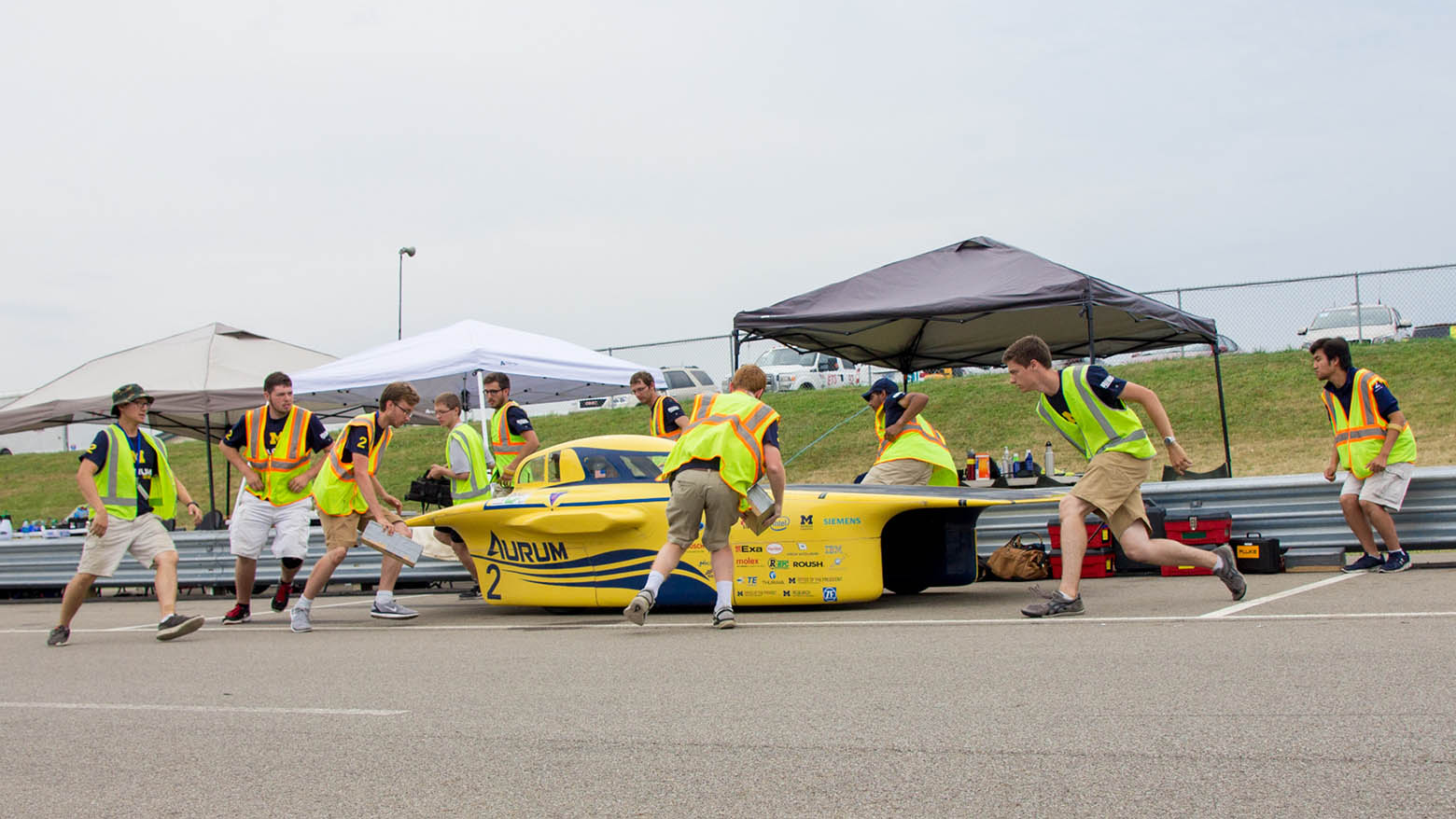 Members of the Michigan Solar Car team race to surround their car, Aurum, during a pit stop at the track.