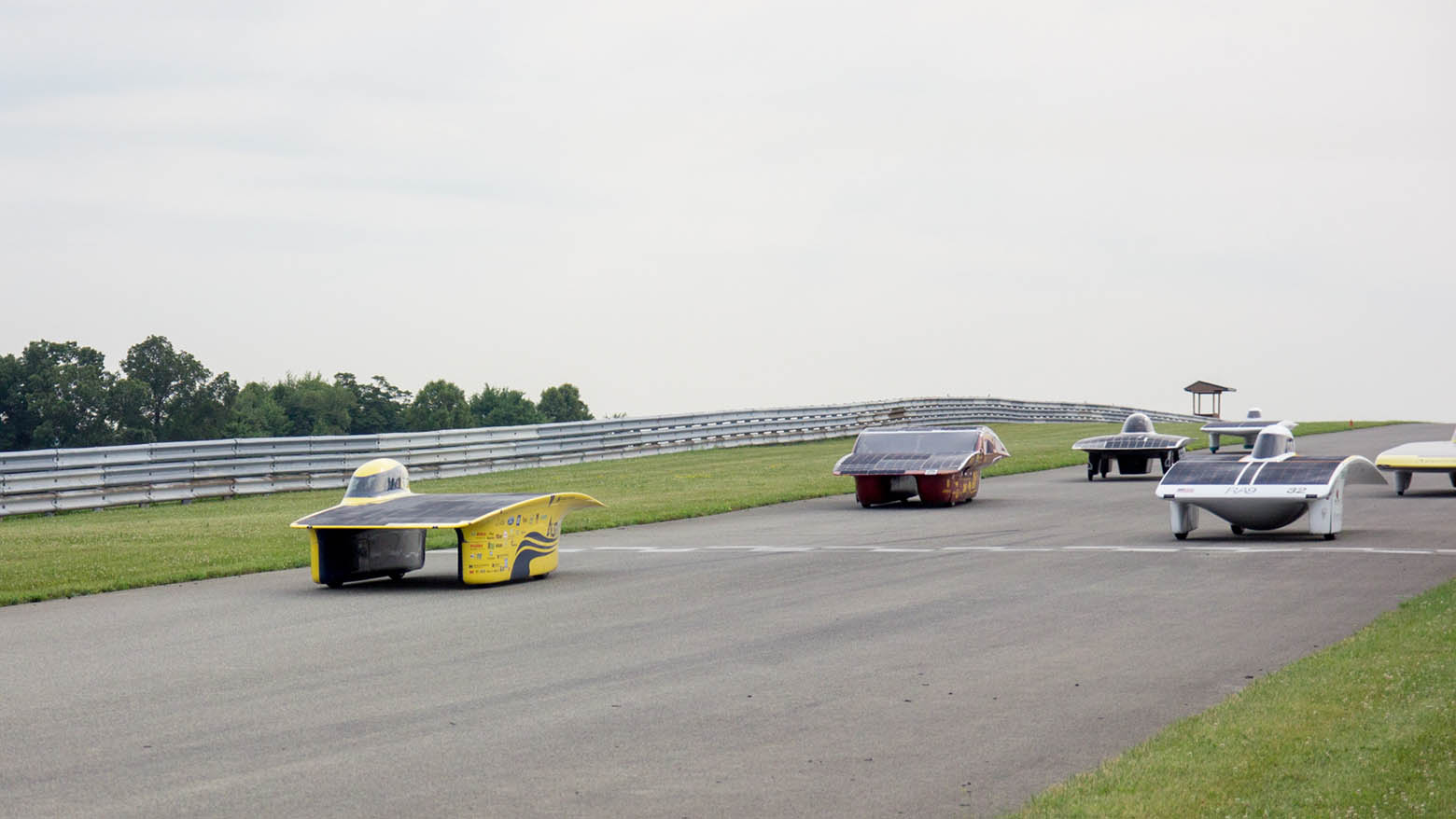 Aurum, the Michigan Solar Car, leads a pack of solar cars across the starting line at a race track.