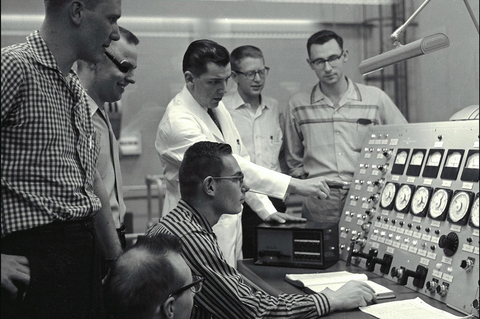 Scientists surround a control panel in 1948