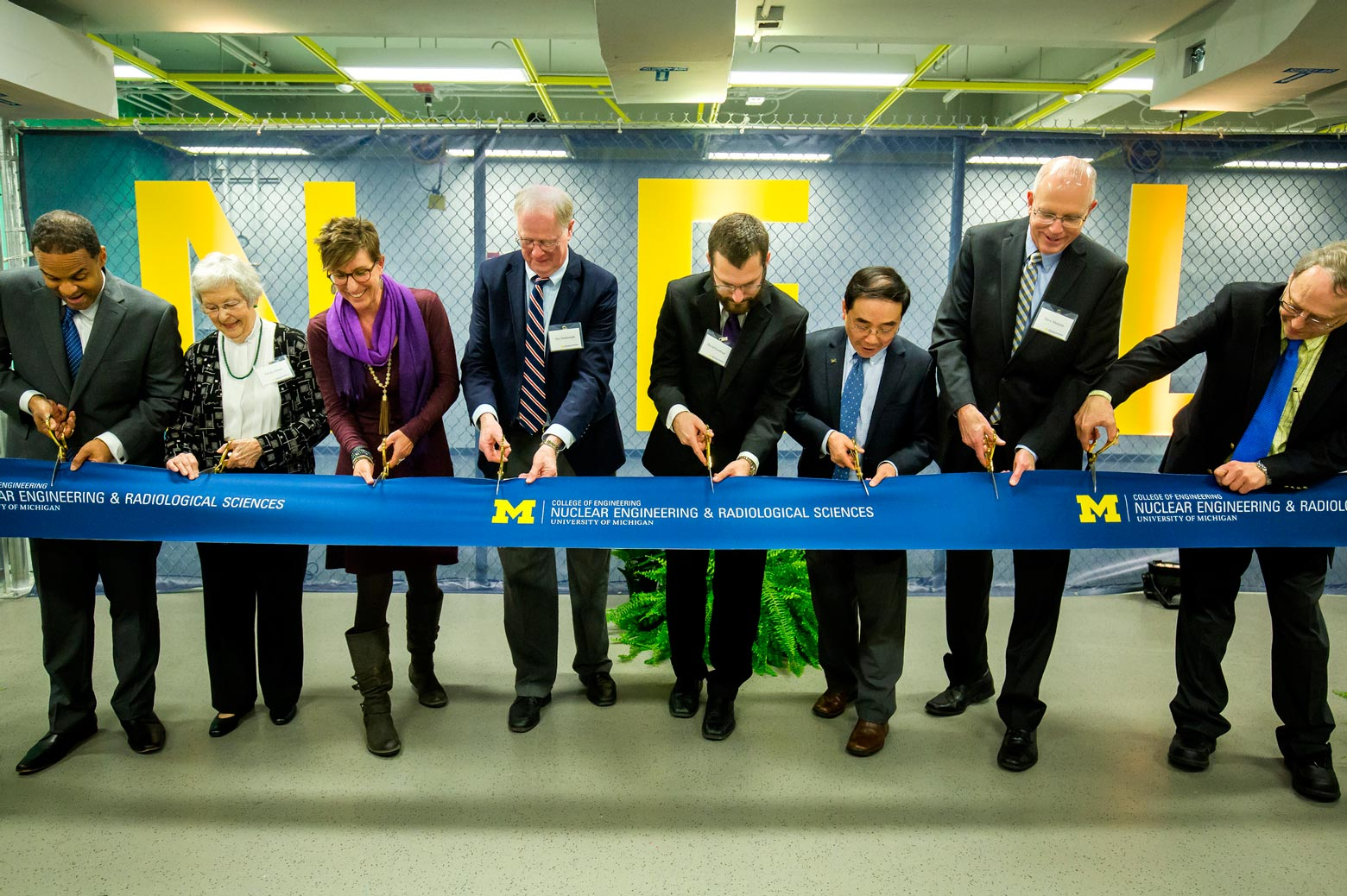 A group of people cut a commemorative ribbon