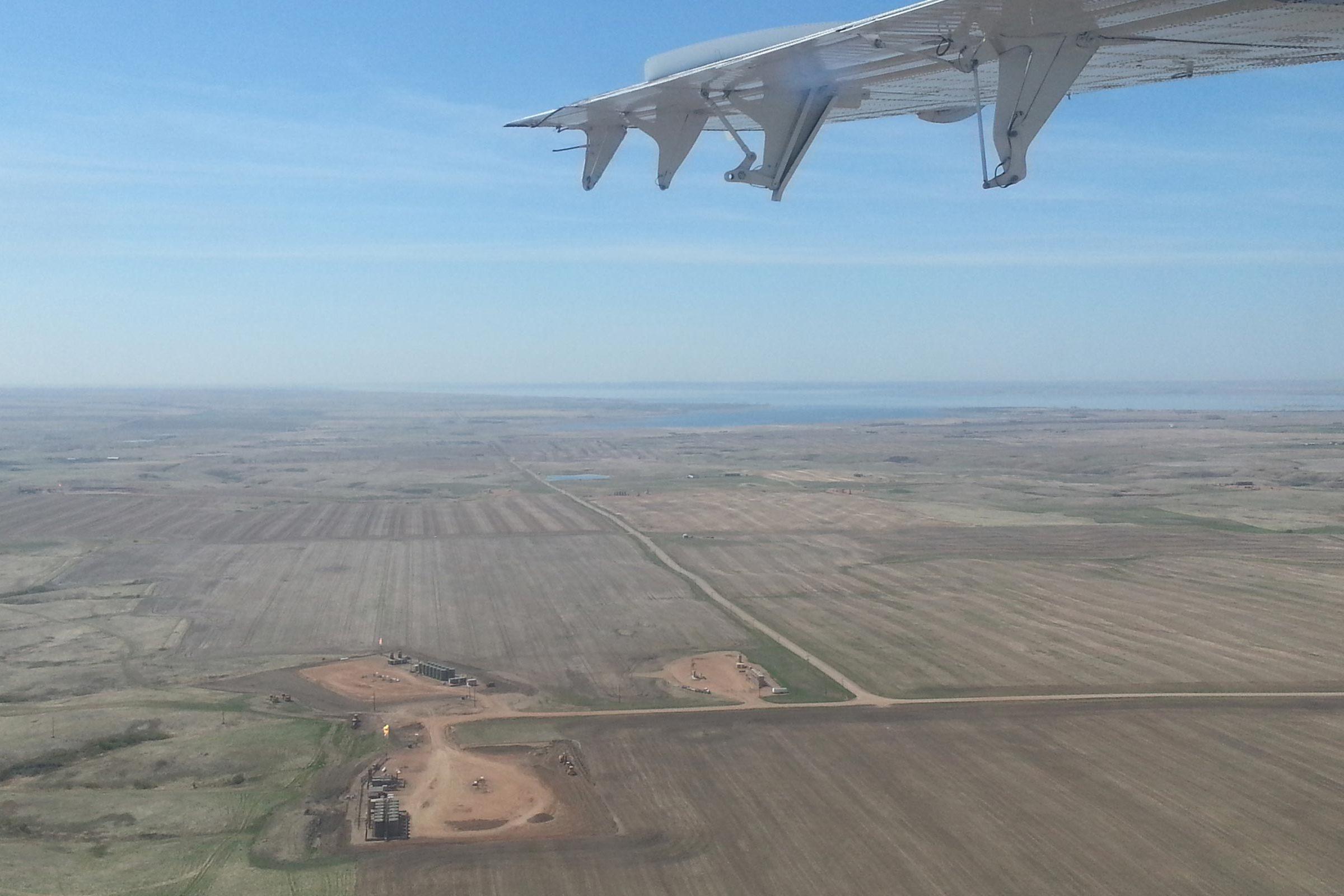 Plane in flight over oil field