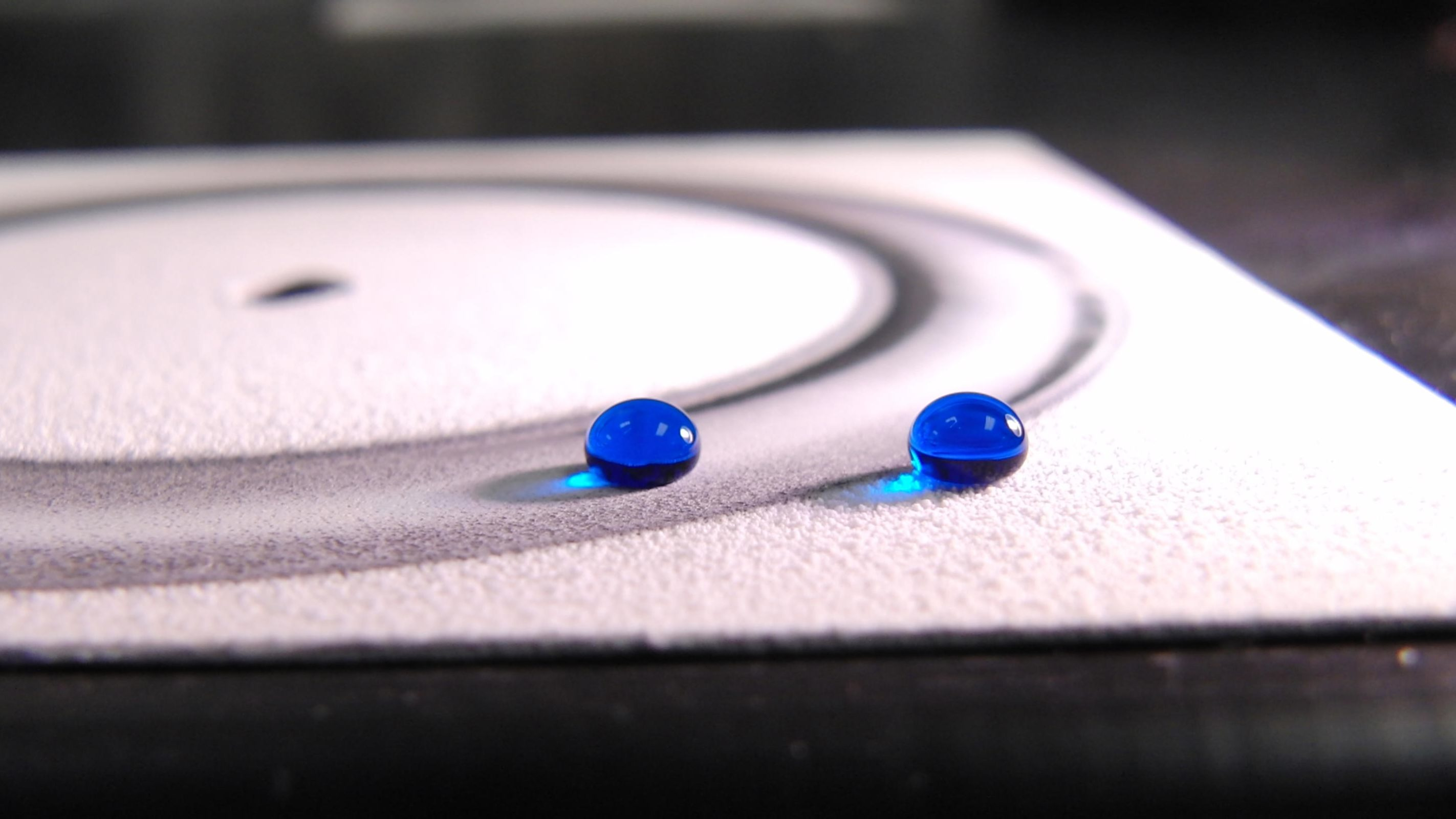 Two droplets of water repelled by an ultra-durable water-repellent coating. The droplet on the left is sitting on a surface that has been abraded by a machine.