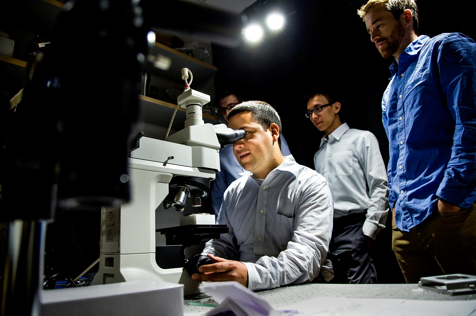 Researcher looks through microscope