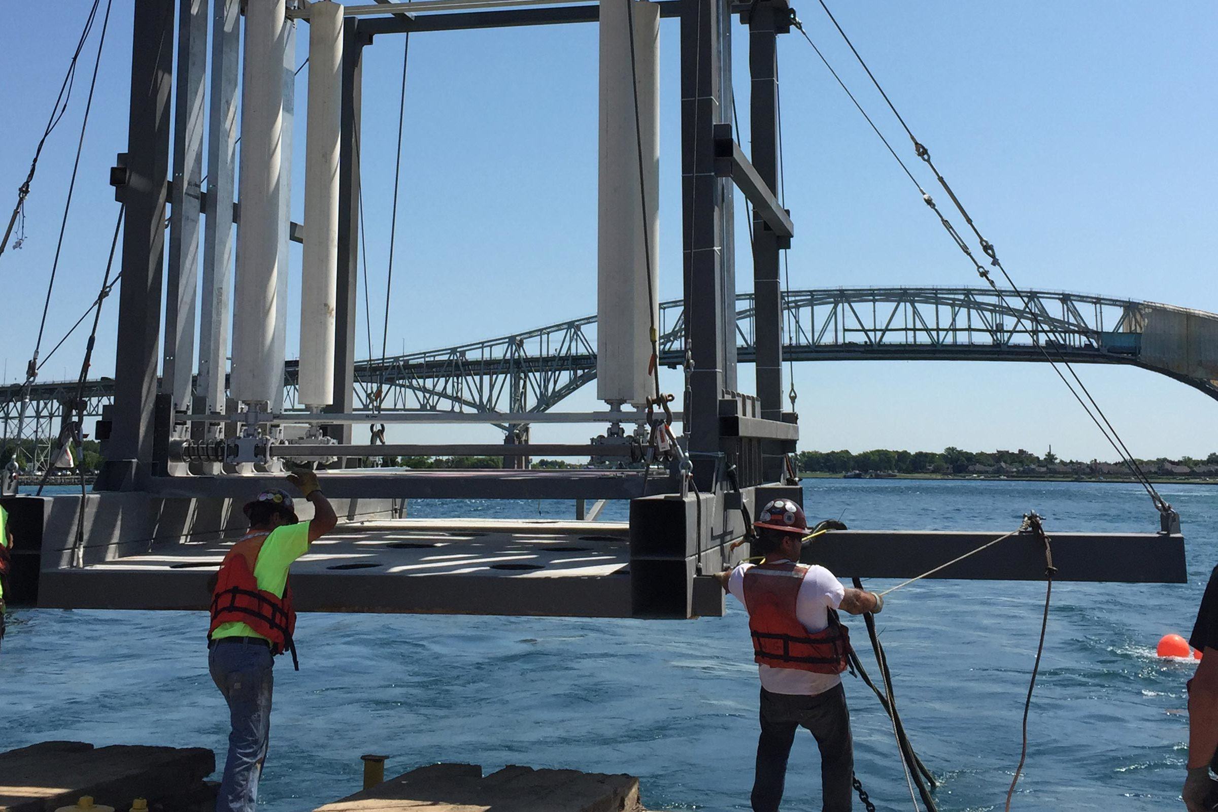 Workers prepare to lower the Vivace device into the St. Clair river
