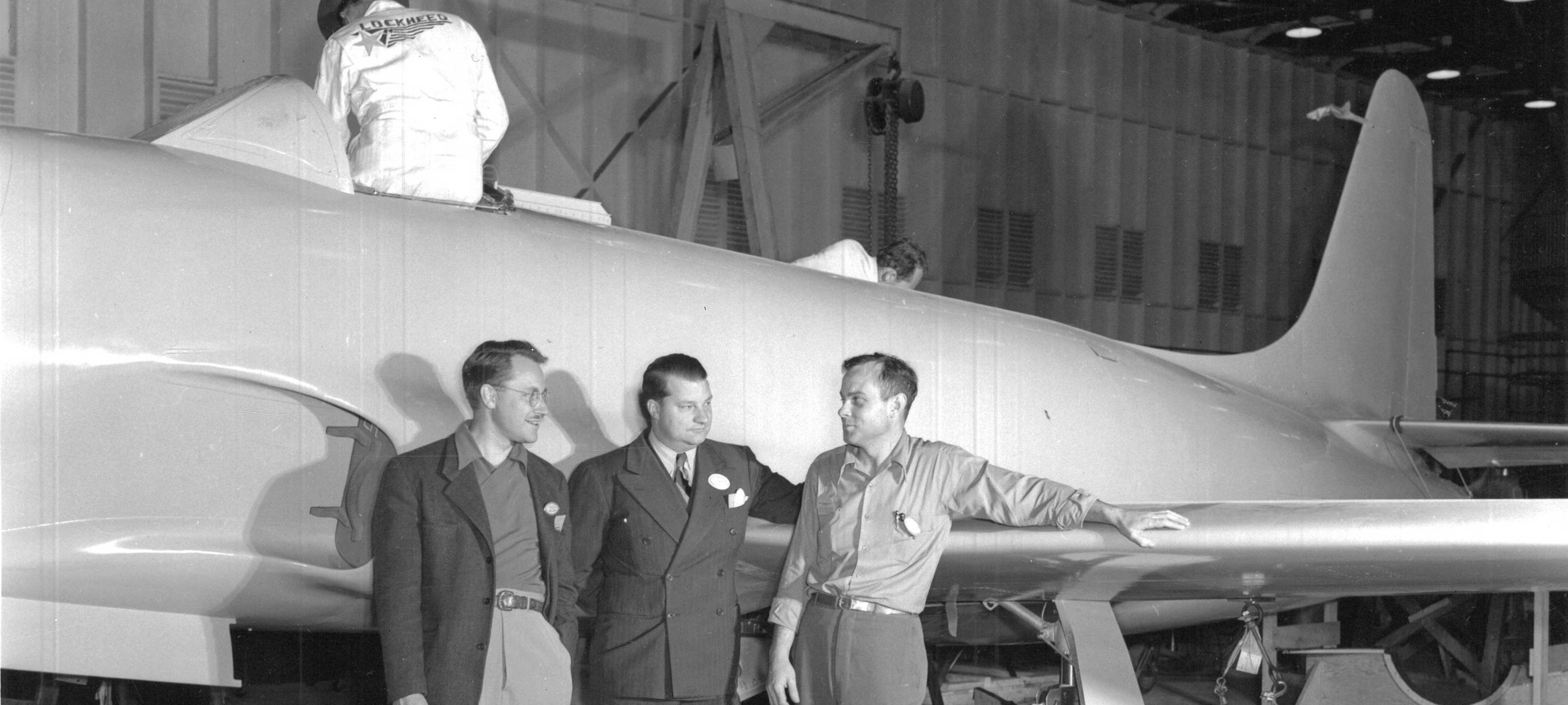 Black and white photo of men near airplane