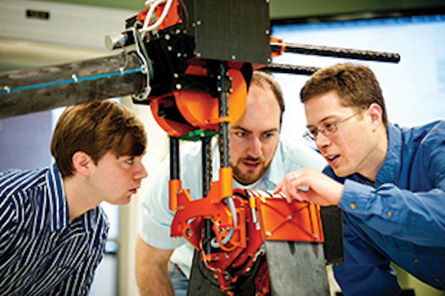 professor and students examining a hip joint of a bipedal robot