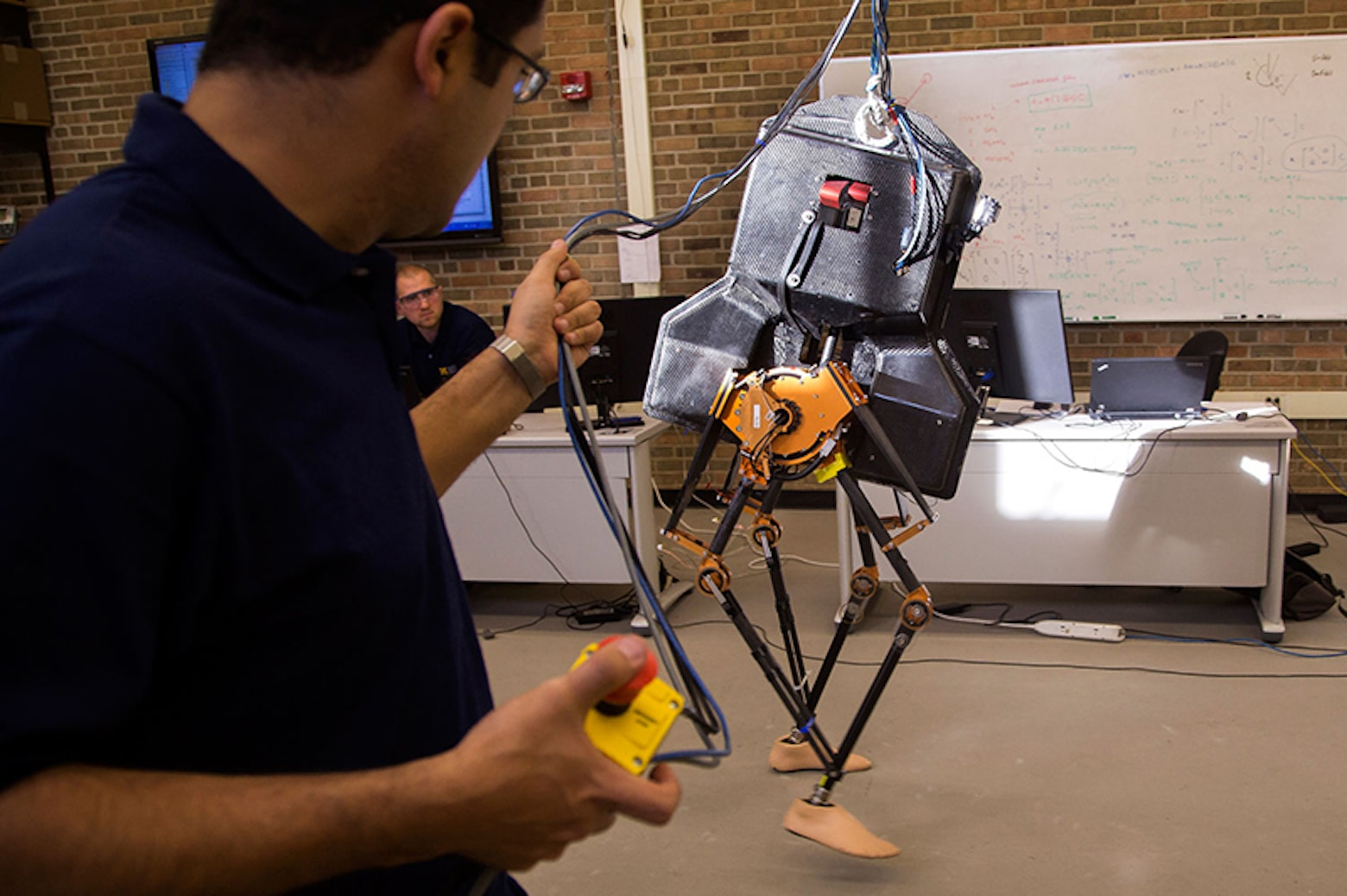 Research fellow walks MARLO, the college's newest bipedal robot.