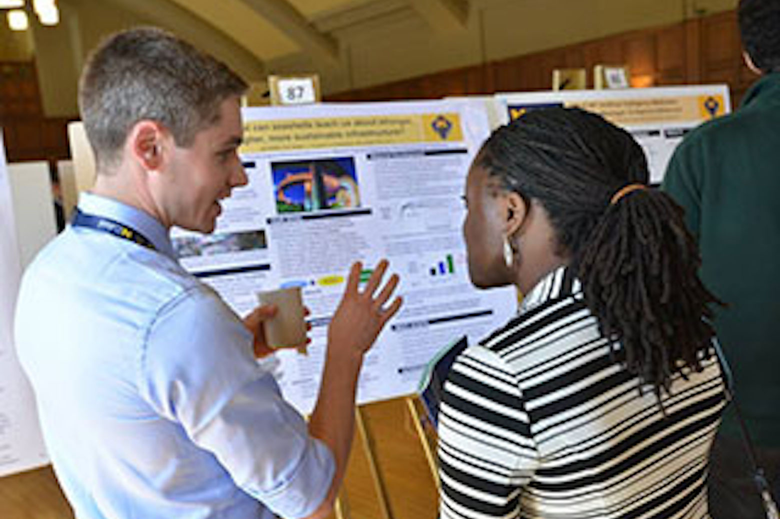 2 participants talk while looking at a poster proposal