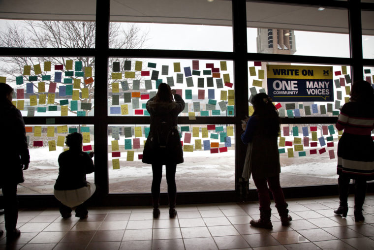 A photograph of students writing messages of inclusion and openness in the Duderstadt Connector