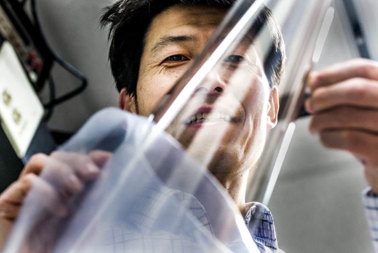 A photograph of EECS Professor L. Jay Guo holding a stainless silver layer.