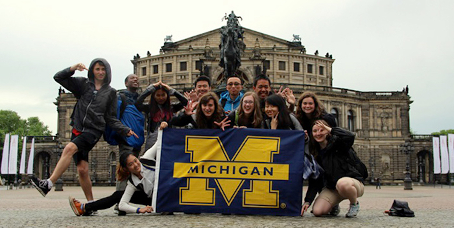Michigan Engineering students pose with a Block M flag in Berlin.