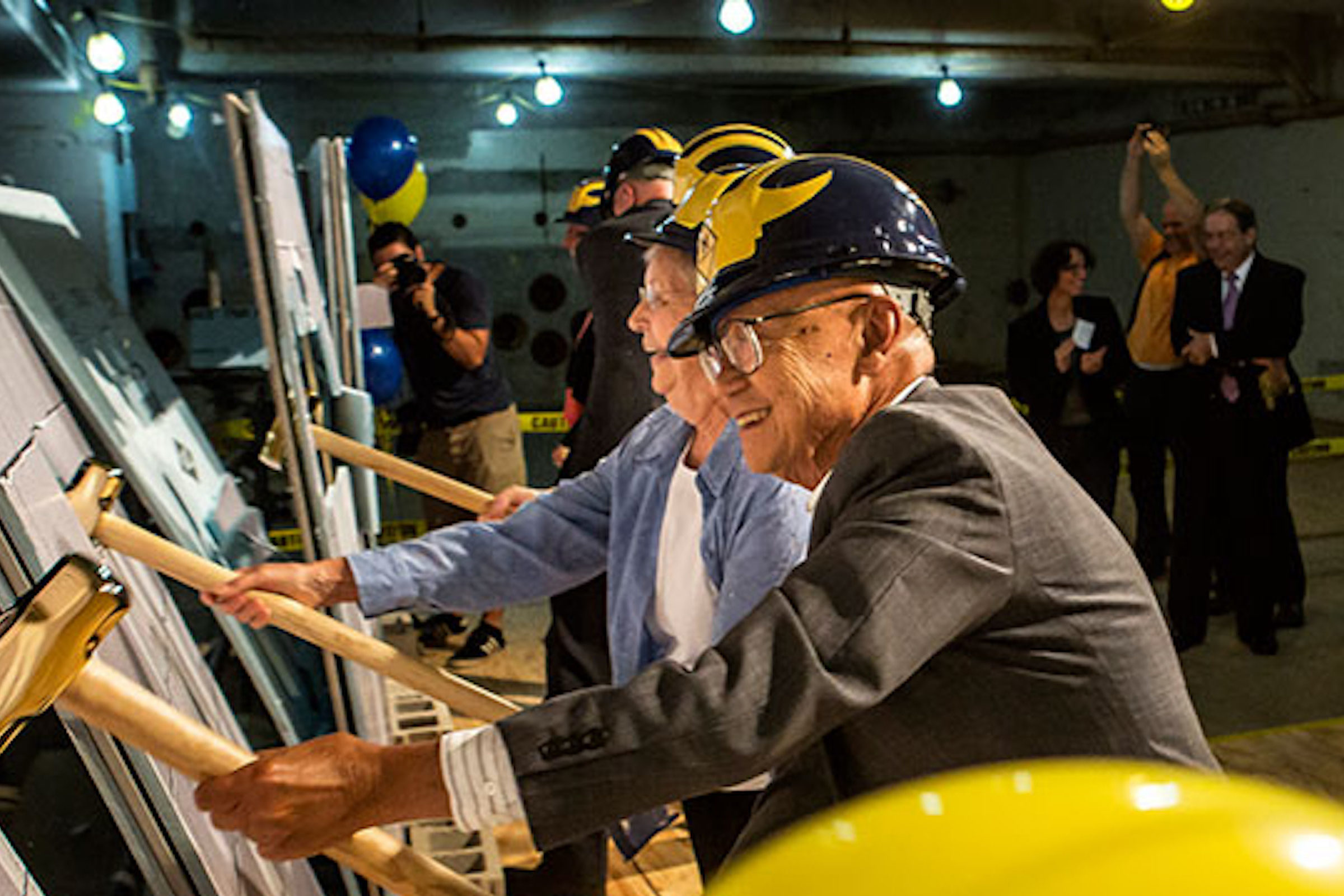 Important people in U-M Engineering break the wall with gold hammers