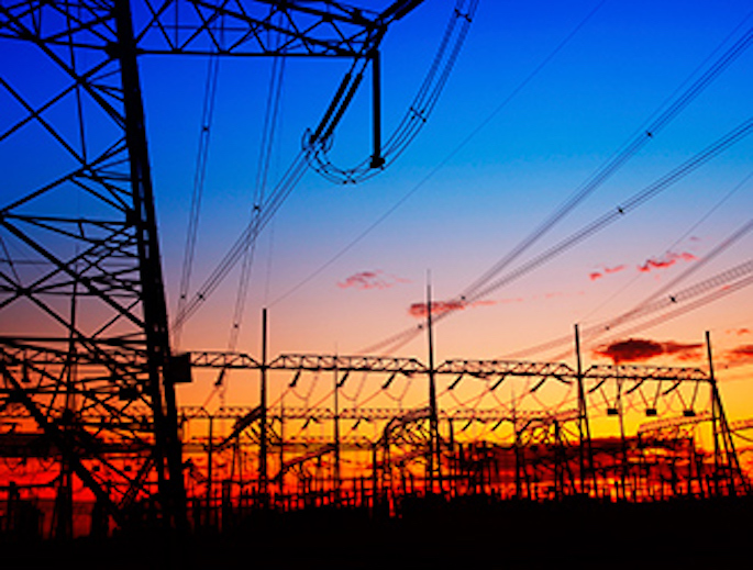 Powerlines with colorful sunset in the background.